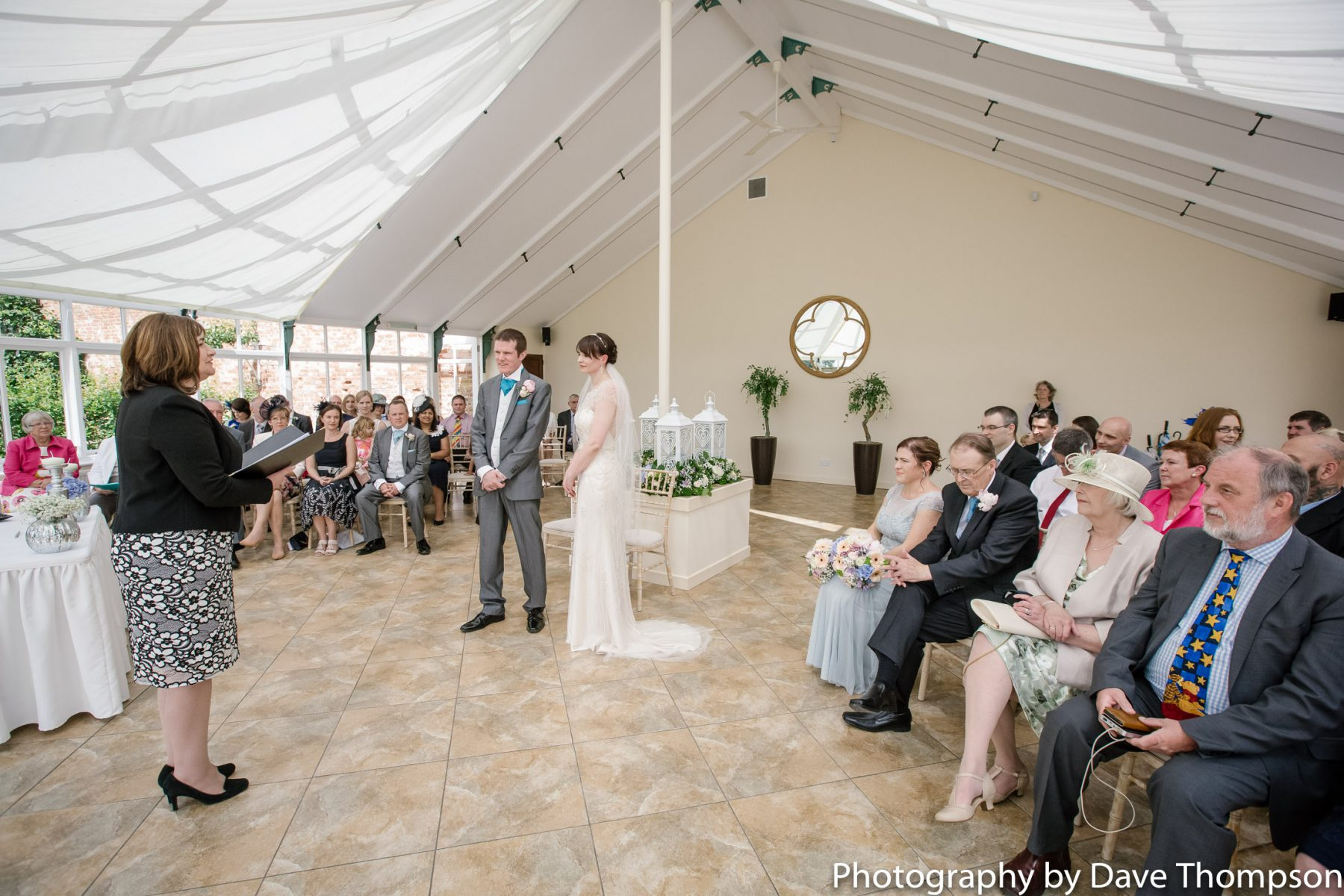 A wedding ceremony in The Edwardian Glass House at Combermere Abbey