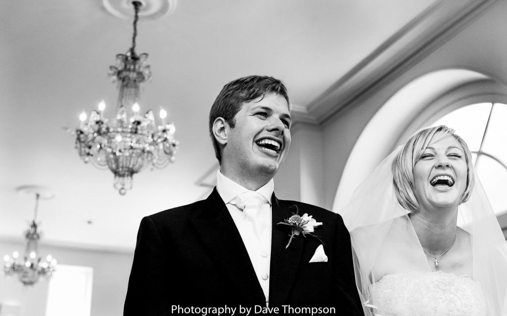 The bride and groom laugh as they begin saying their vows