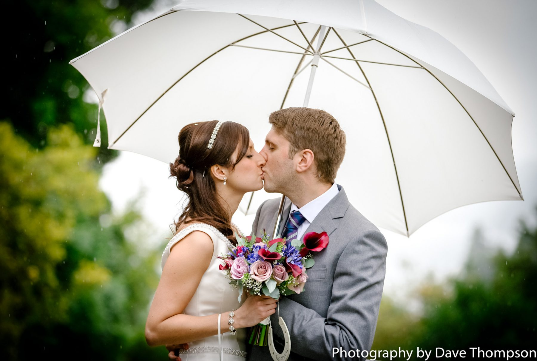 Bride and groom beneath an umbrella