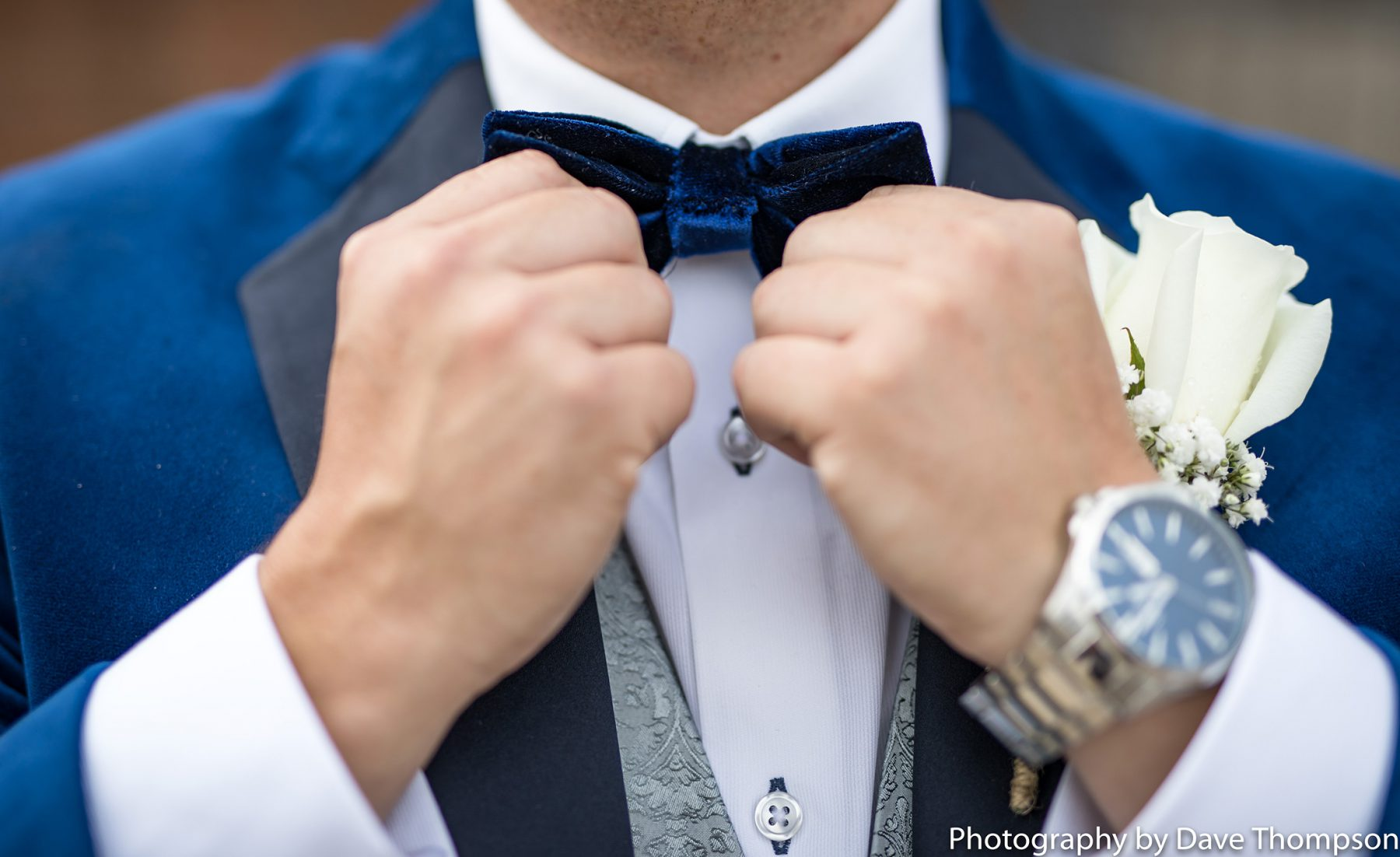 The groom adjusts his bow tie