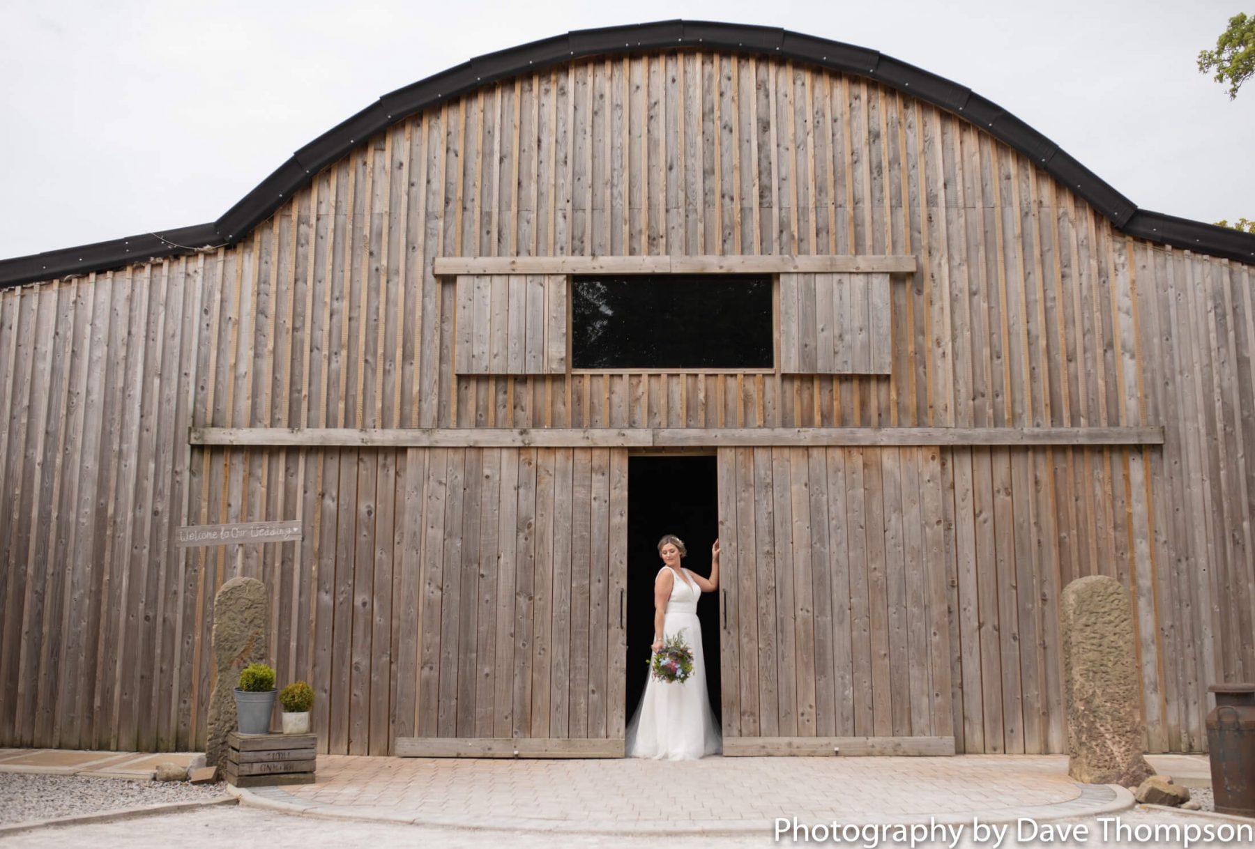 A bride in the doorway of Alcumlow Barn wedding venue