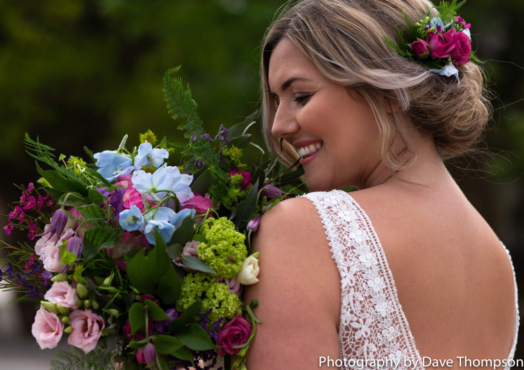 A bride smiles holding her flowers