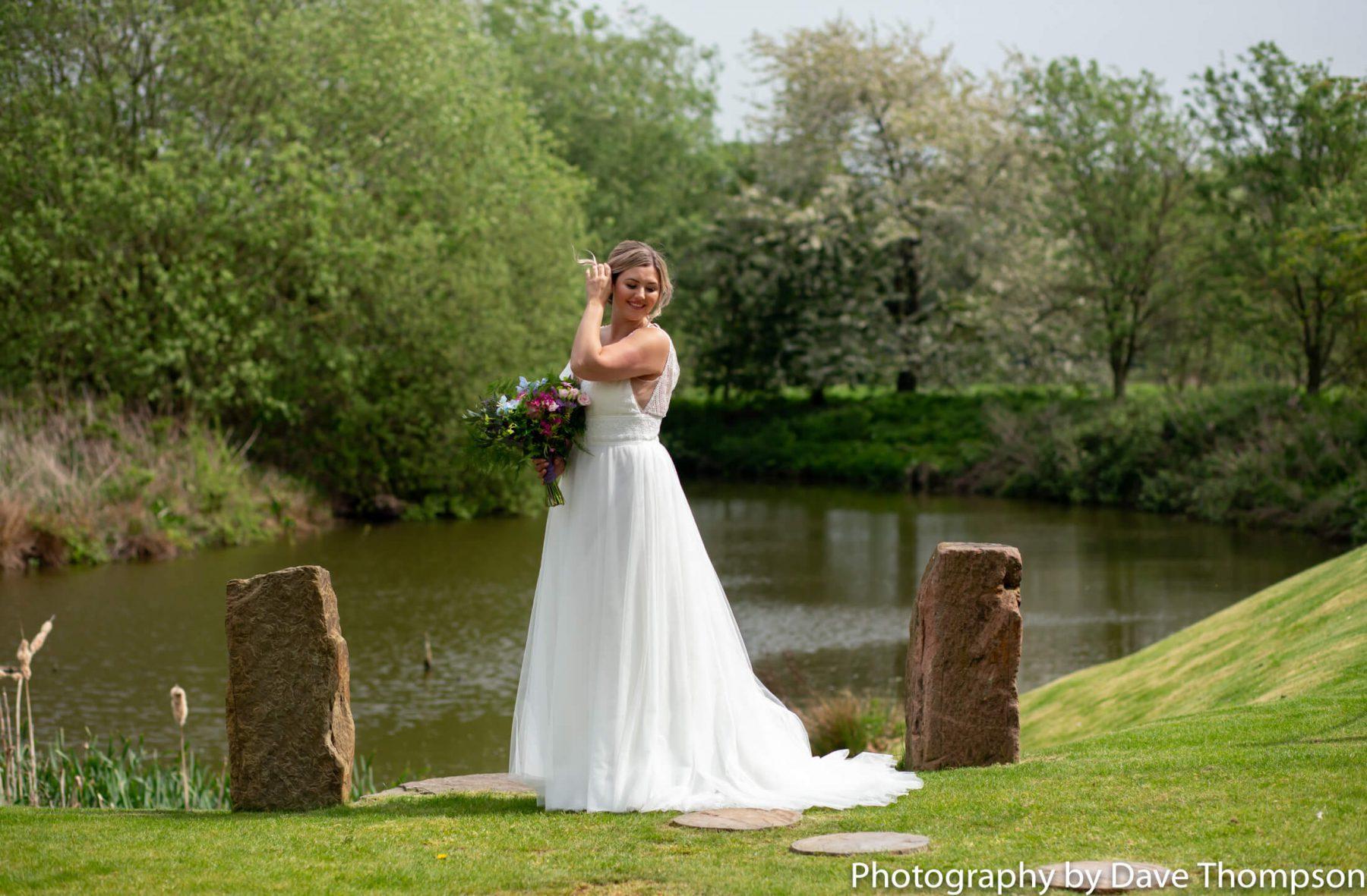 Bridal portrait by the lake at Alcumlow Barn wedding venue