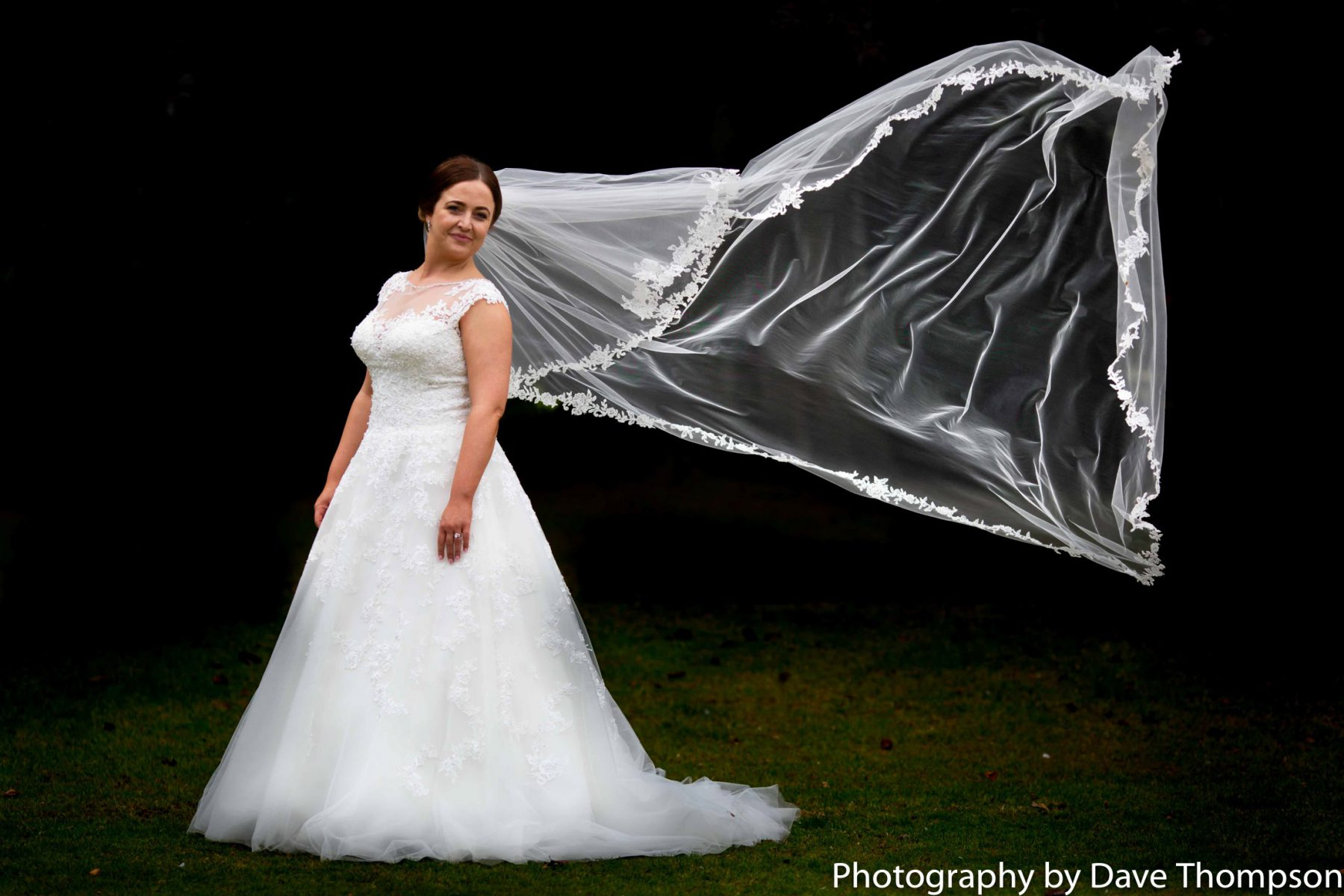 The bride in her dress as the veil flies behind