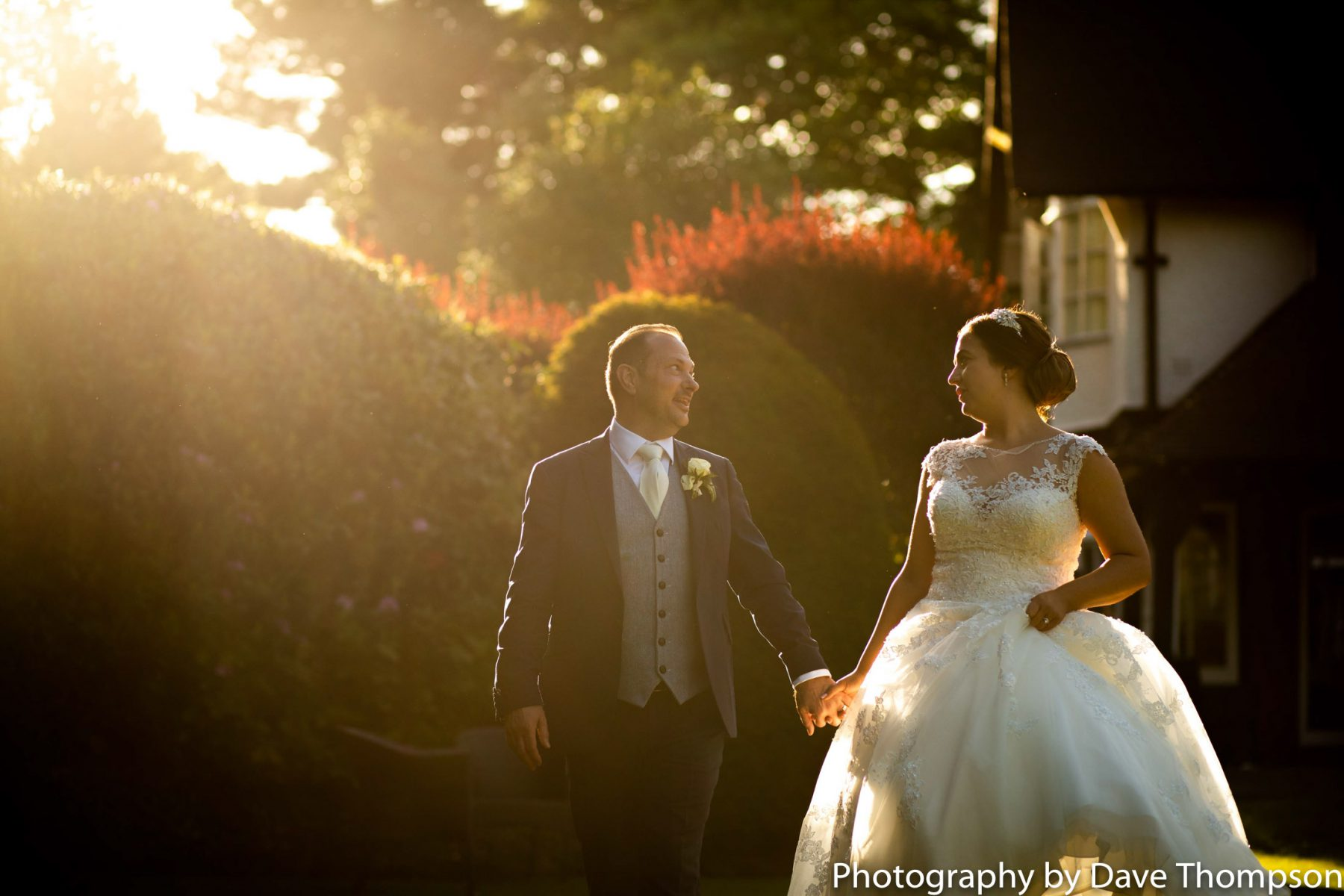 The bride and groom go for a walk in early evening sunshine