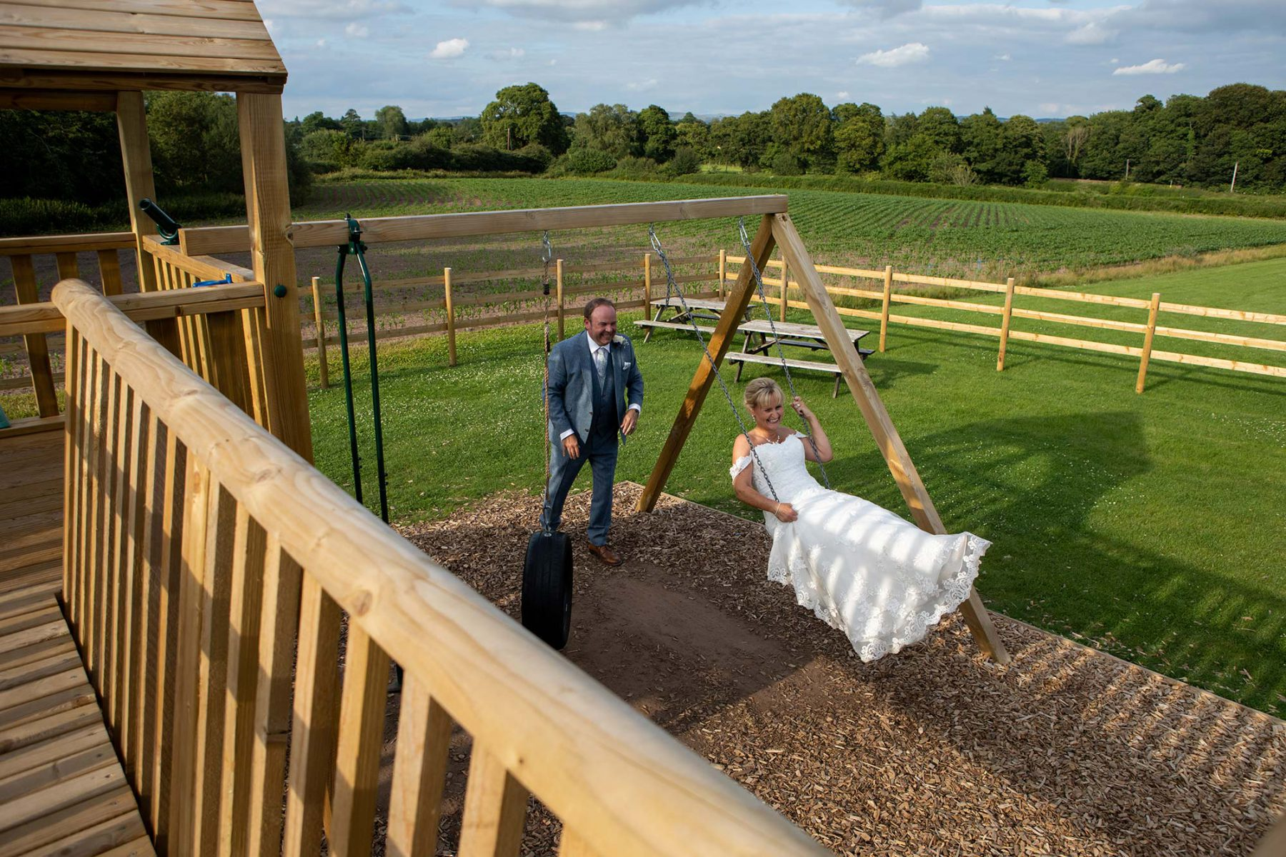 the groom pushes his bride on a swing
