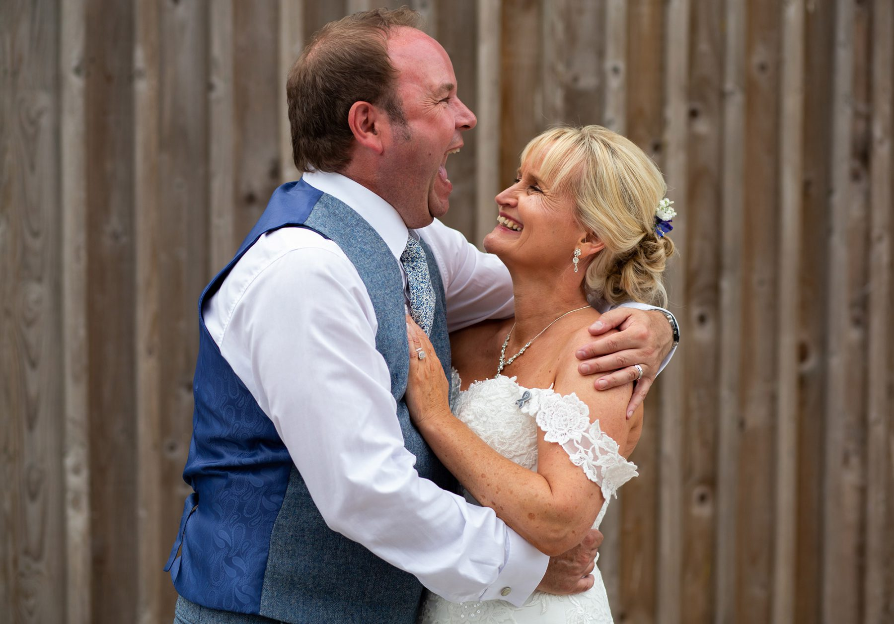 The bride and groom laughing as they hug