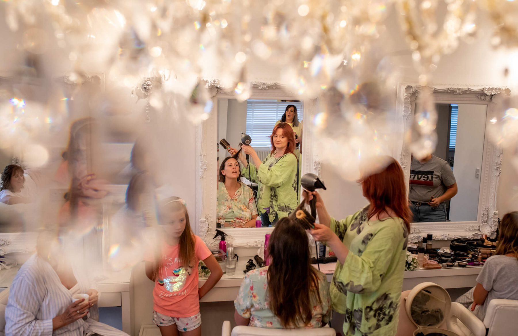 The bride having her hair done during bridal prep