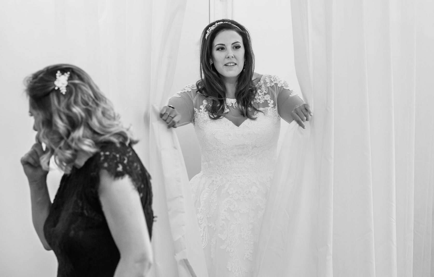 The bride appears in her dress from behind a curtain