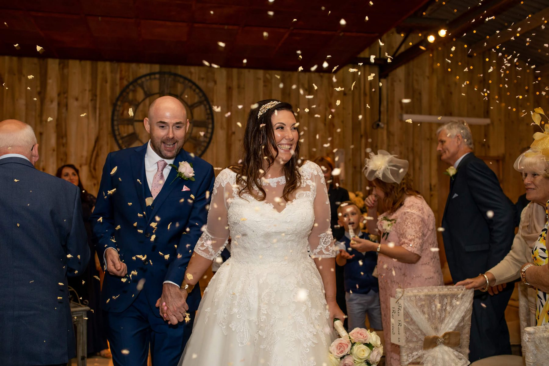 Confetti is thrown as the bride and groom leave the ceremony room.
