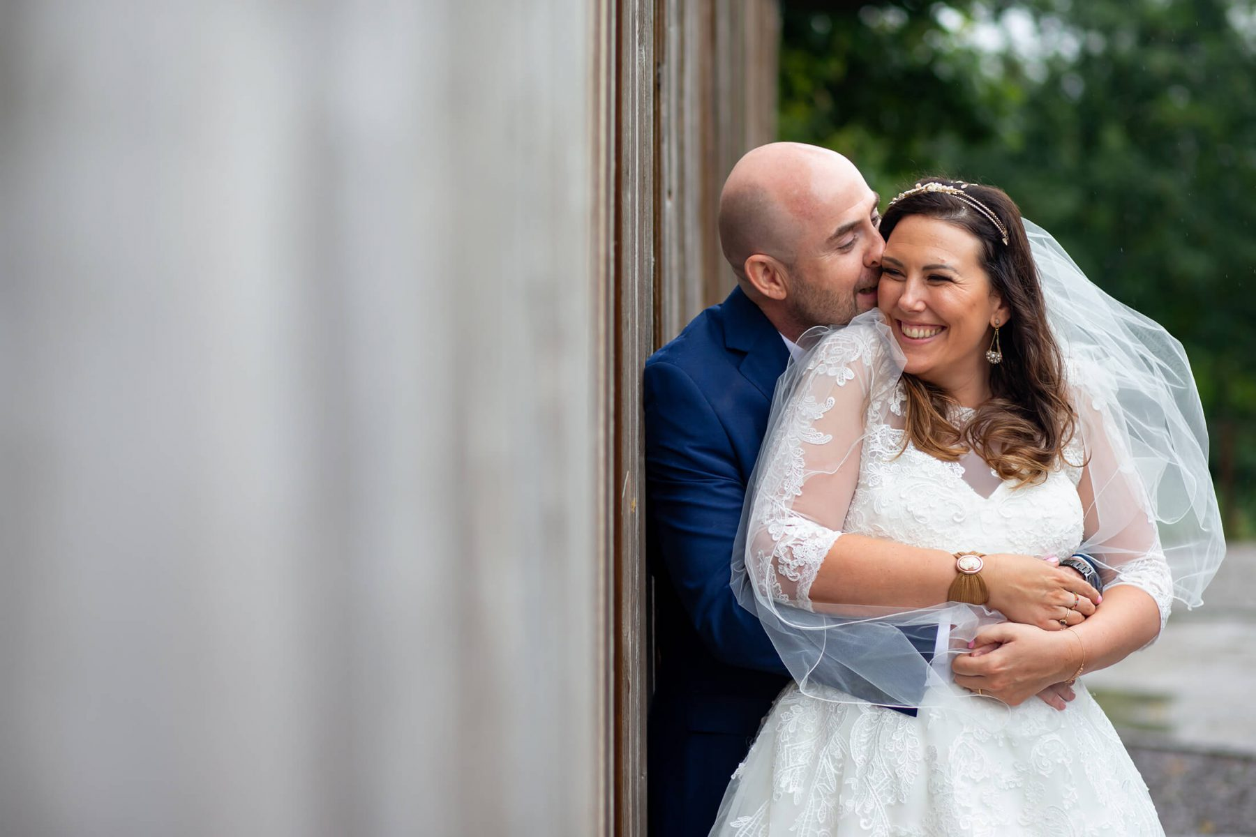 The bride and groom cuddle after their ceremony