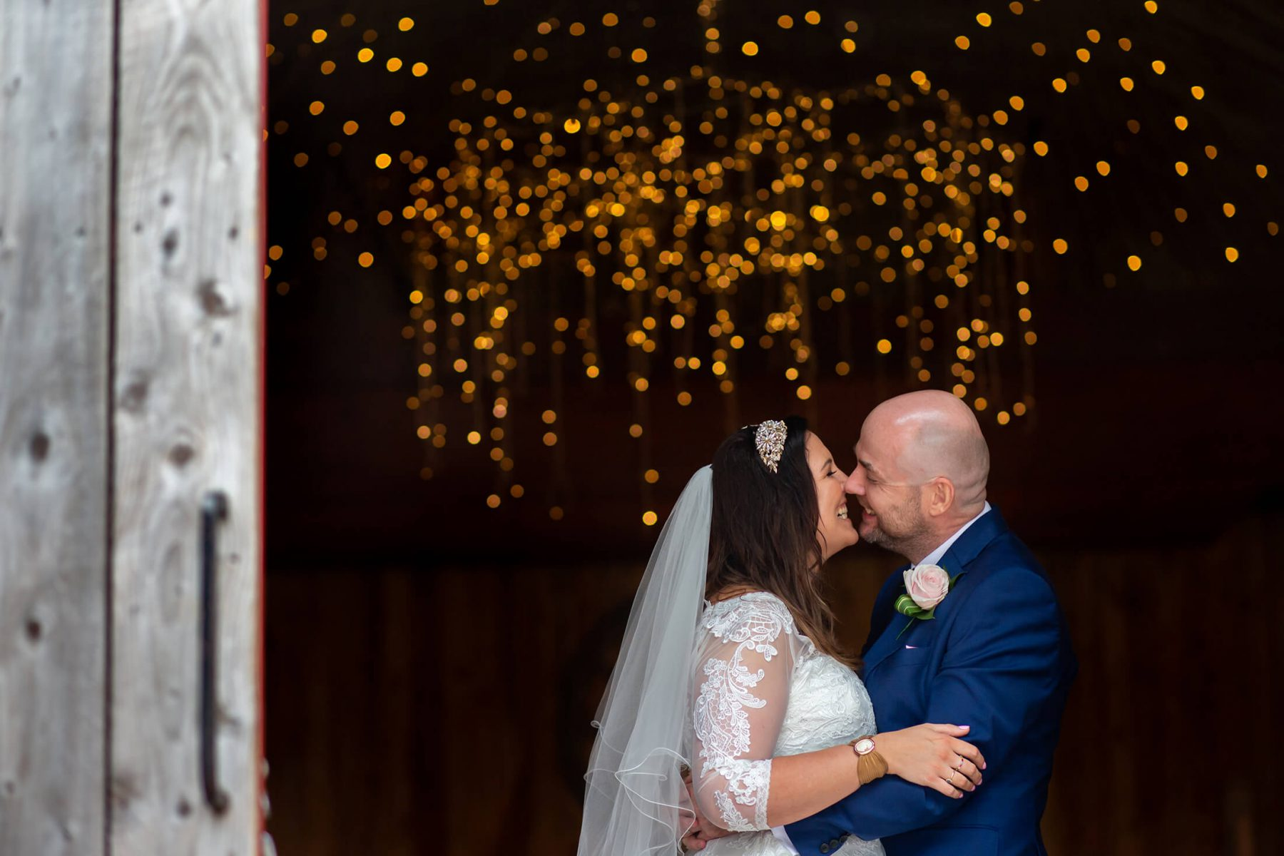 The bride and groom beneath fairy lights in the barn