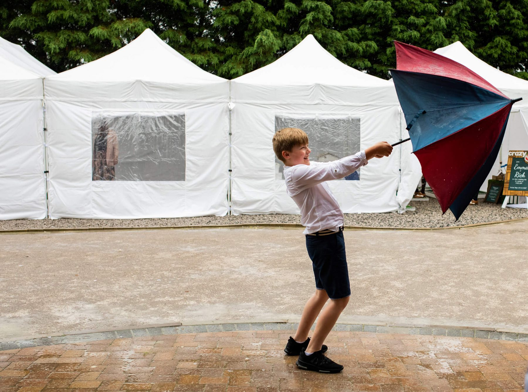 A young buy holds an umbrella