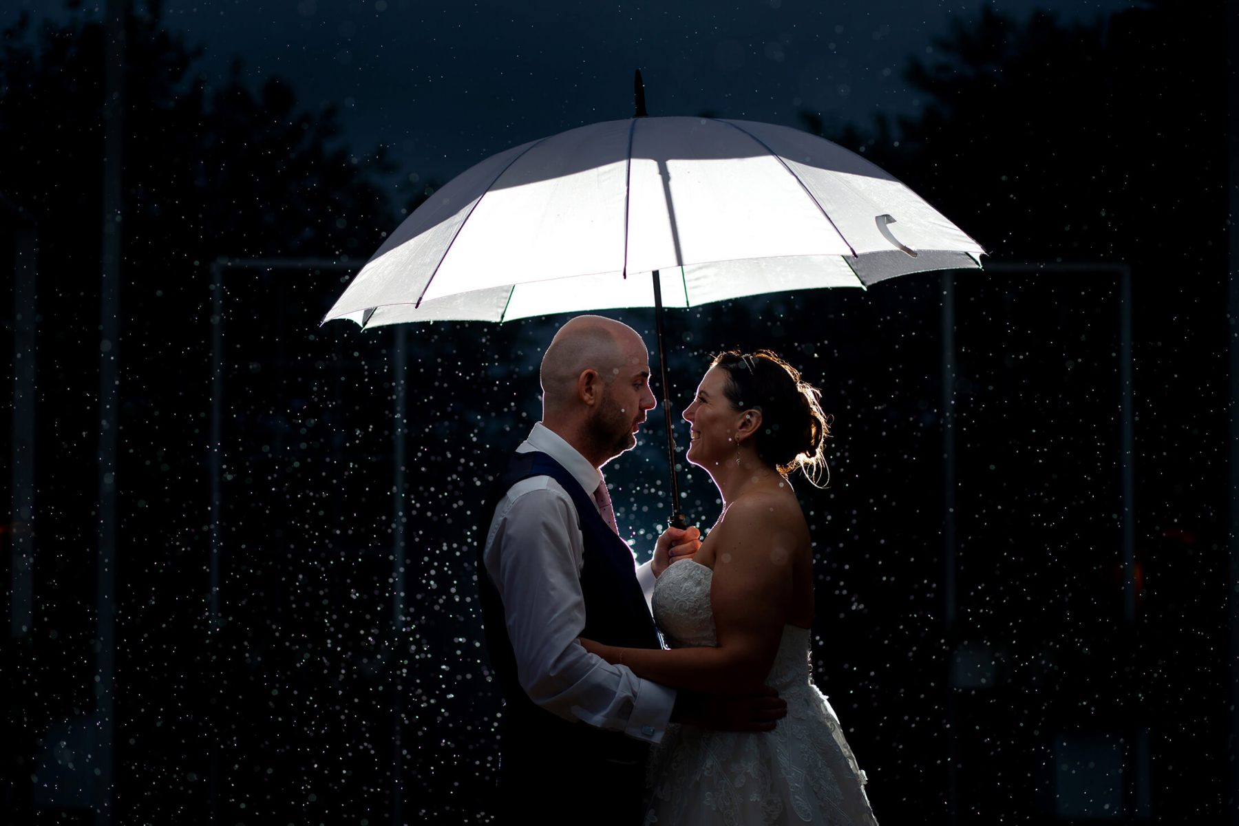 The bride and groom beneath an umbrella in the rain