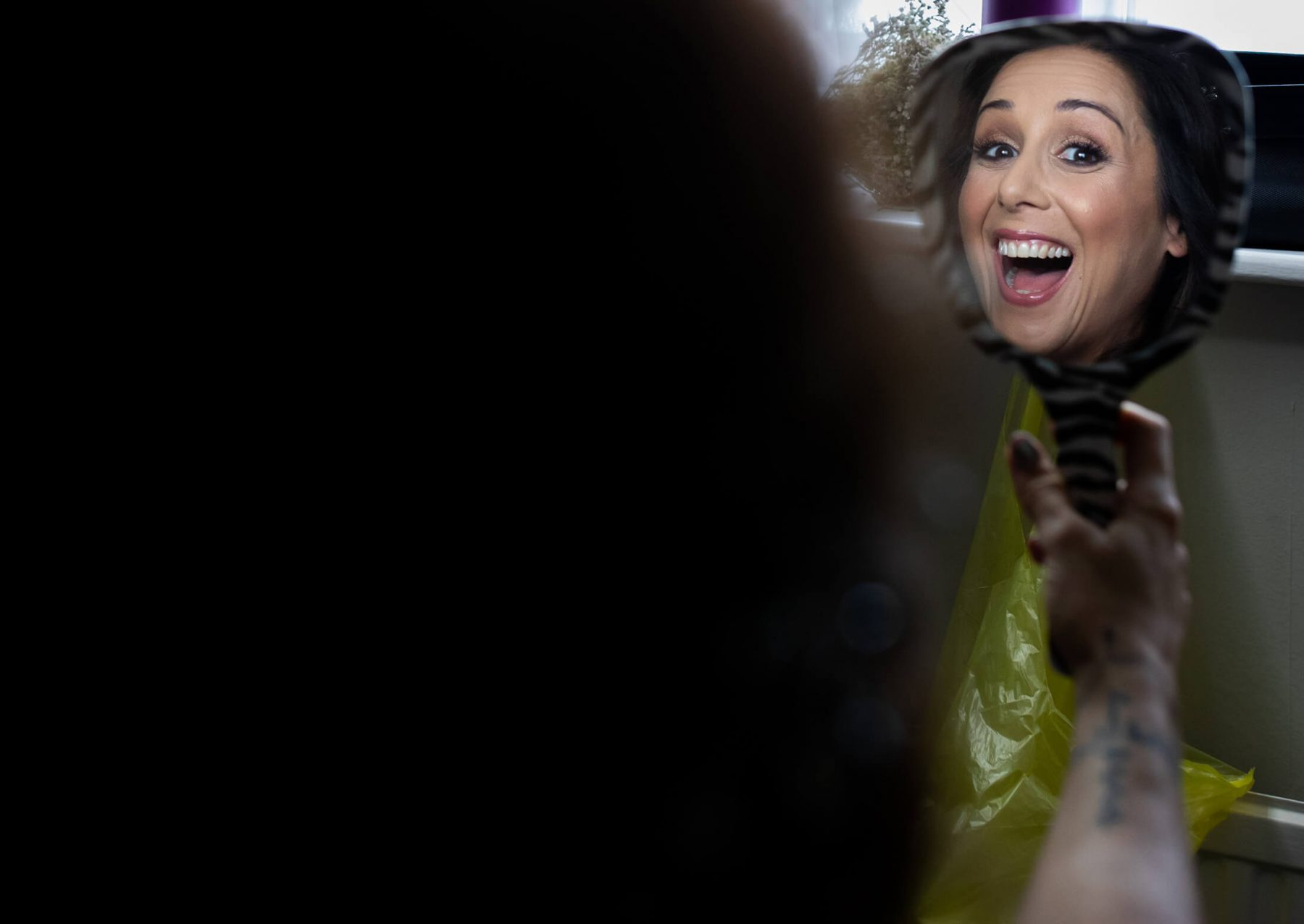 The bride reflected in a mirror after having her make up done