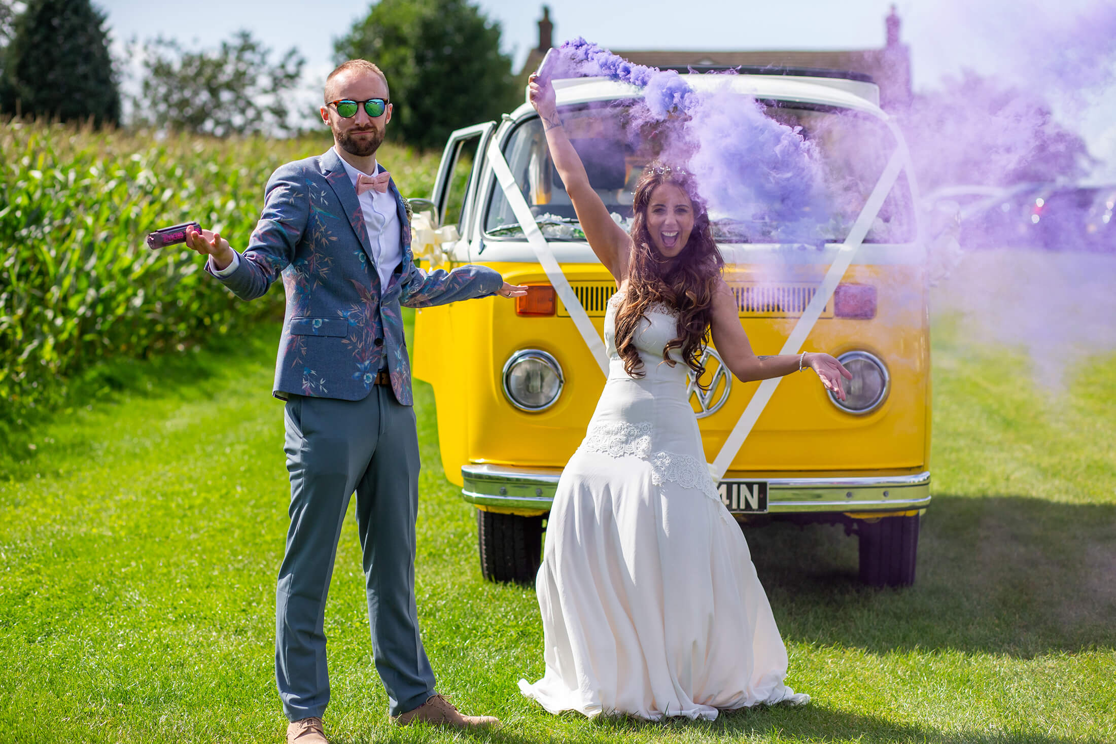 The bride and groom play with smoke grenades