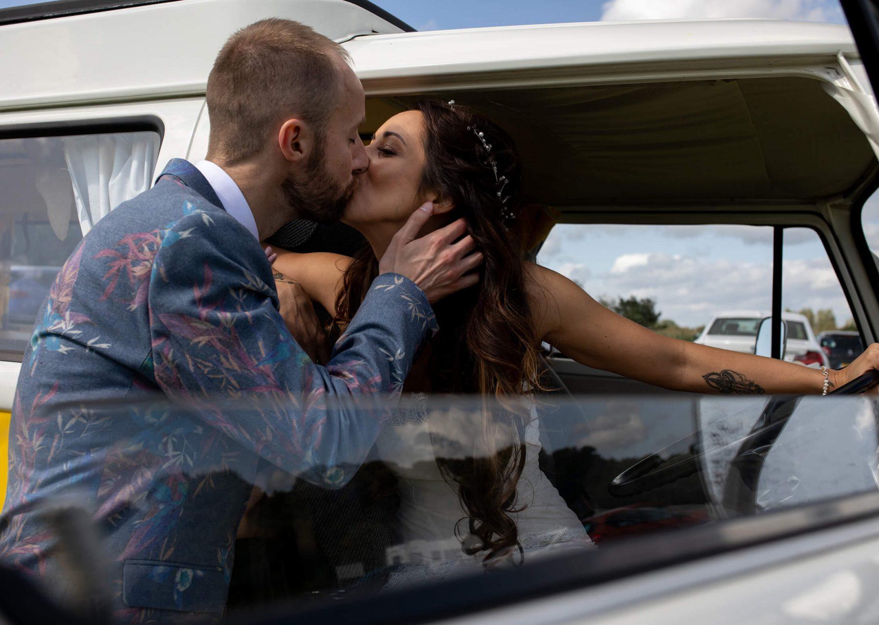 The bride and groom kiss in their VW van