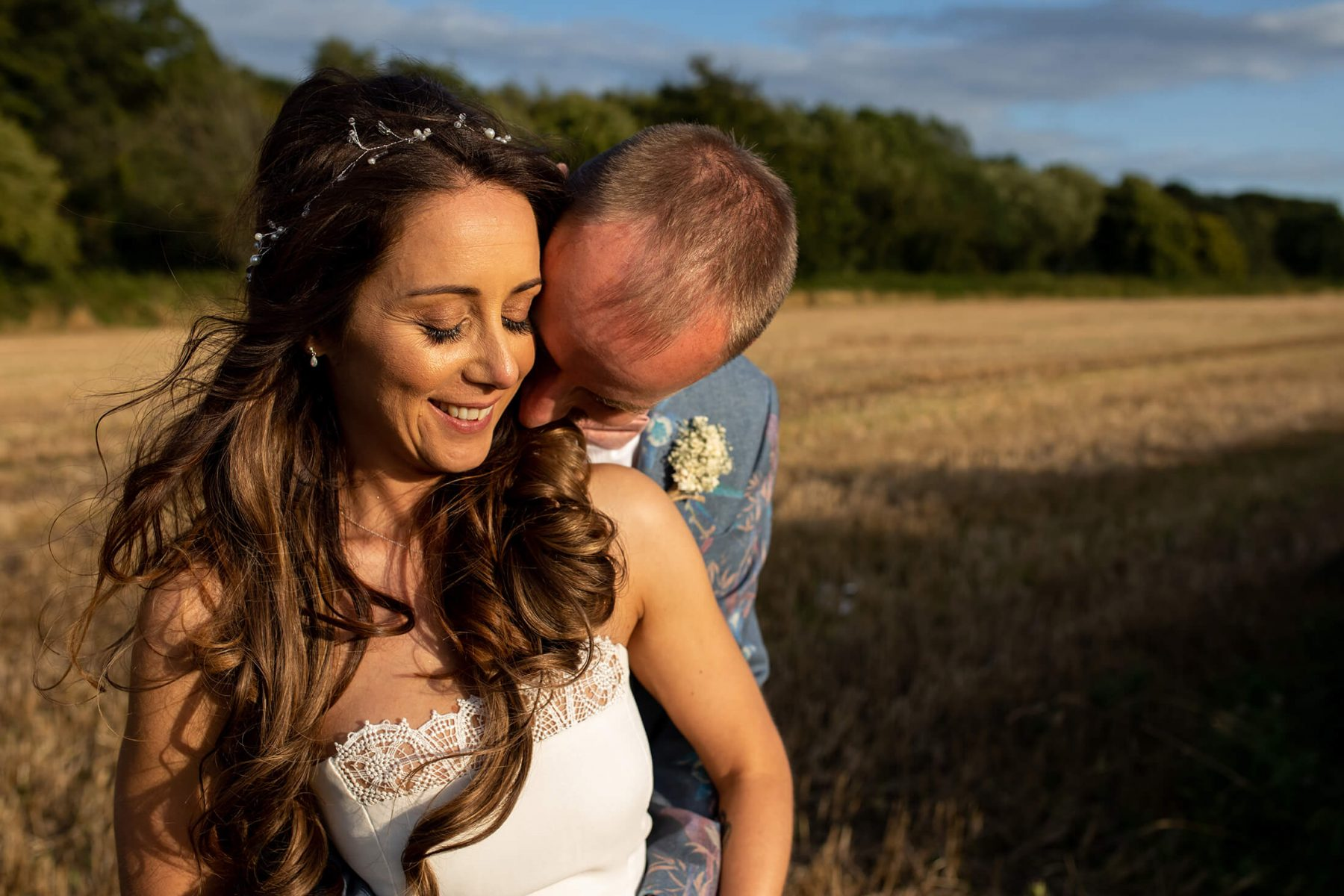 A portrait of a bride and groom in August evening sunlight.