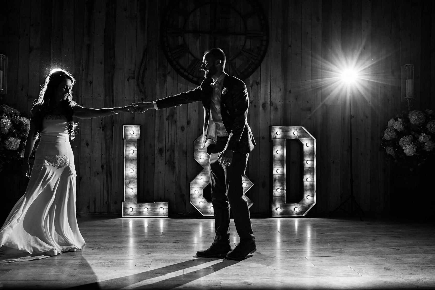 A black and white omage of the bride and groom during their first dance together.