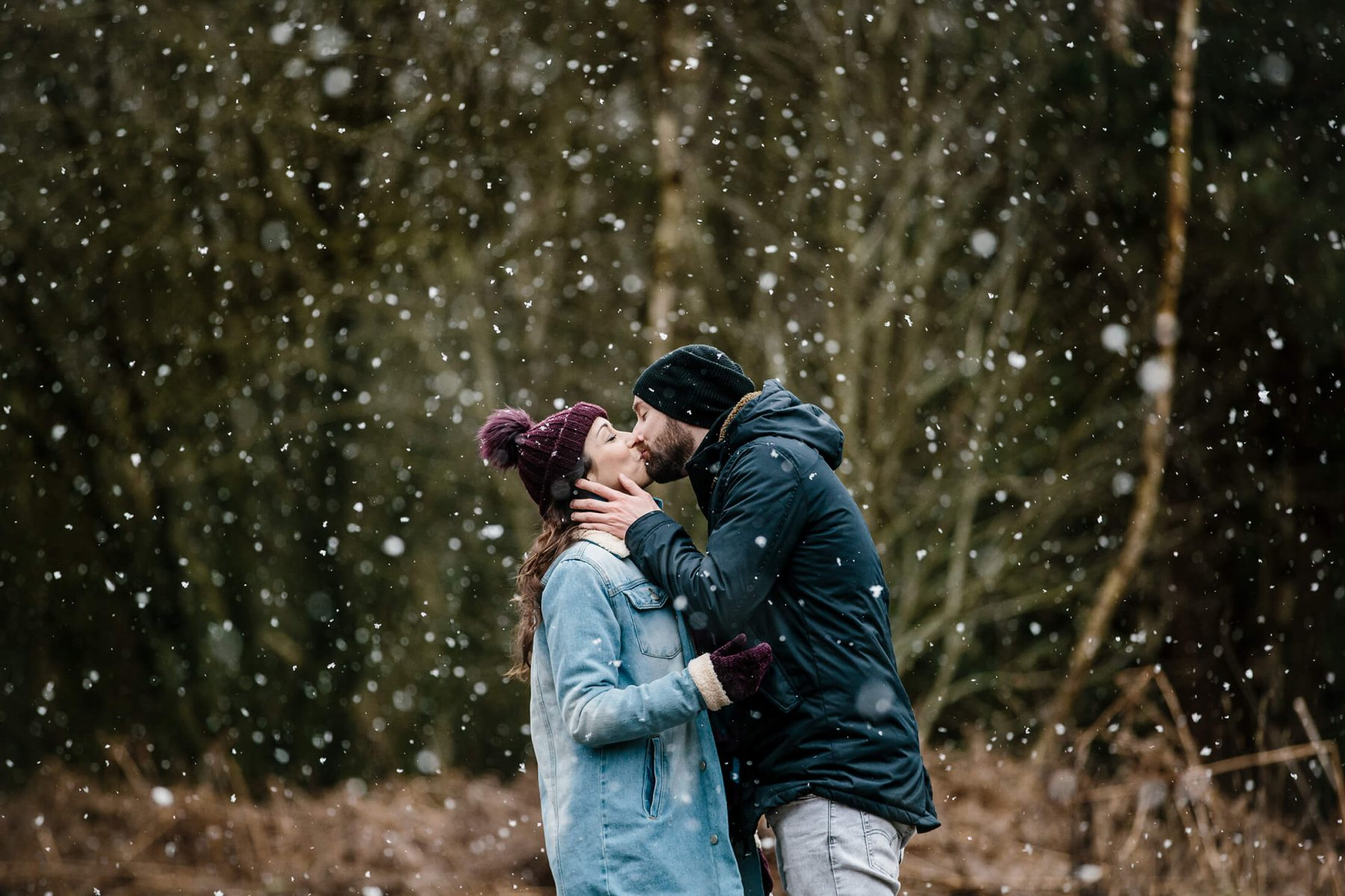 A couple kiss in the snow during a pre wedding photoshoot