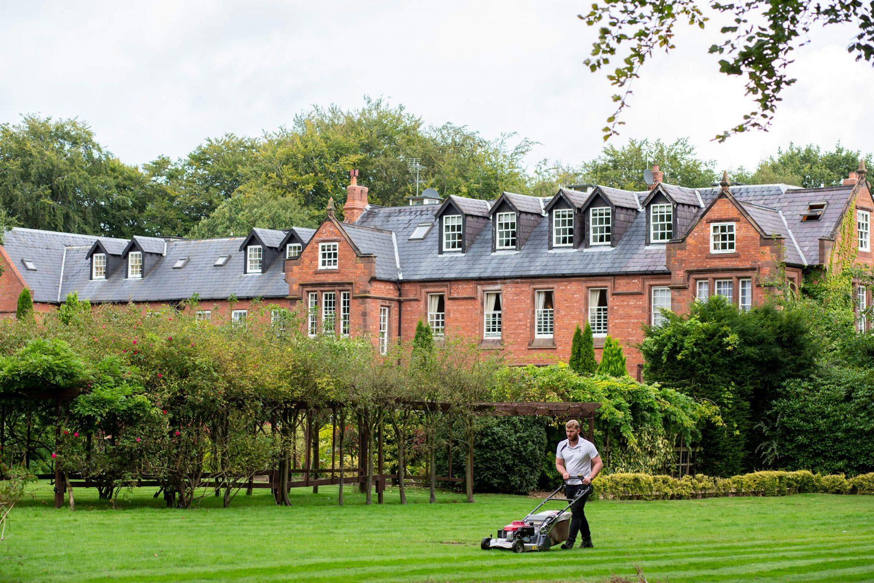 A member of staff mows the lawn outside Nunsmere Hall