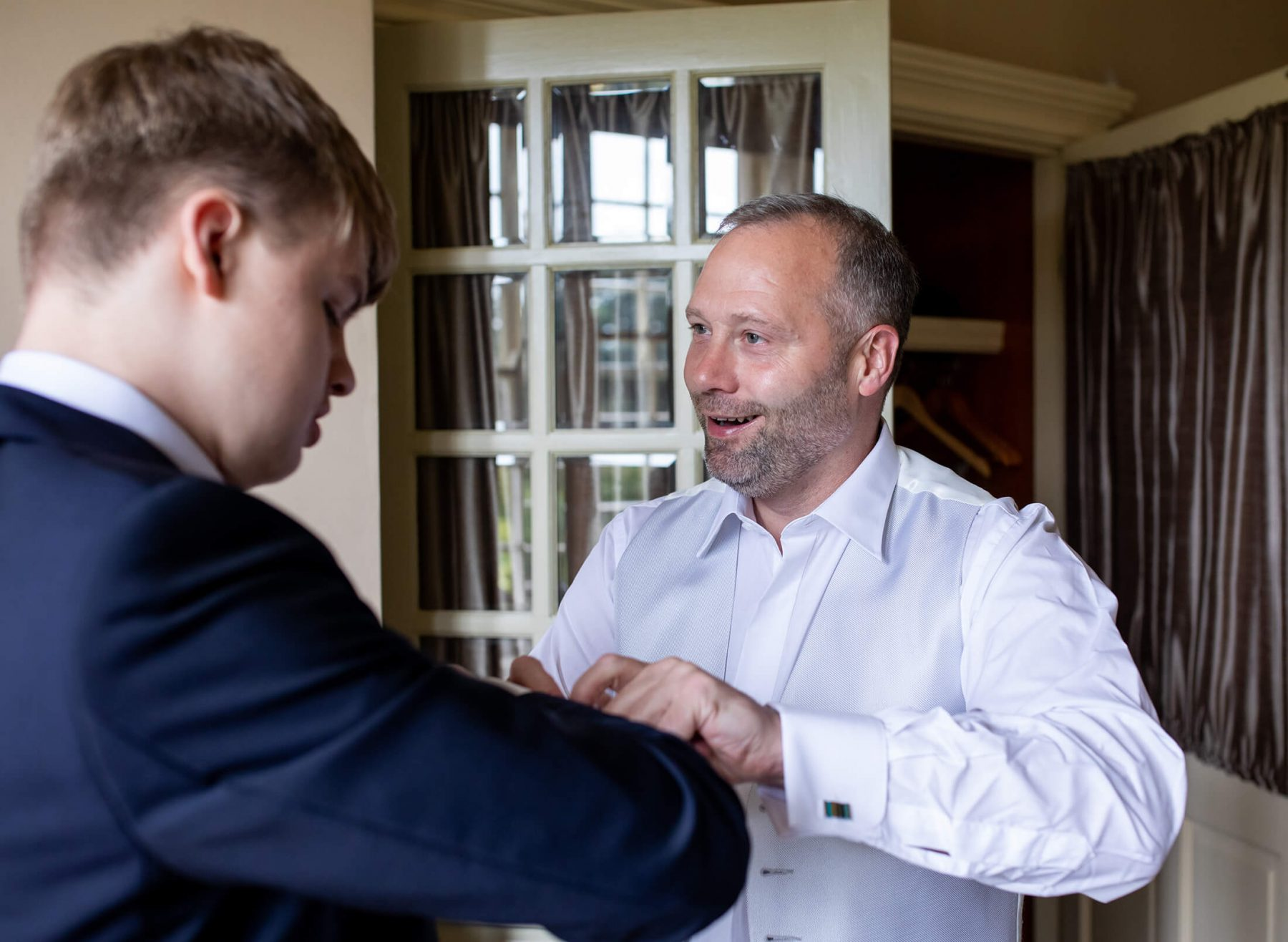 A groom helps his best man with the cufflinks.