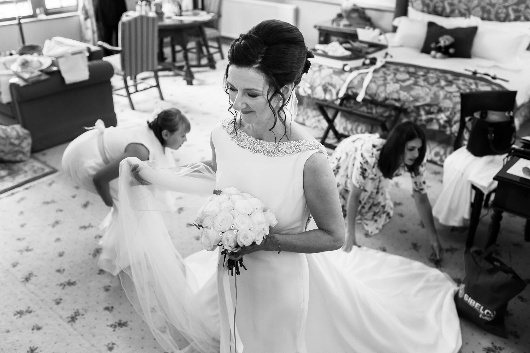 A bride waits as her bridesmaids tend to her dress prior to her wedding at Nunsmere Hall in Cheshire