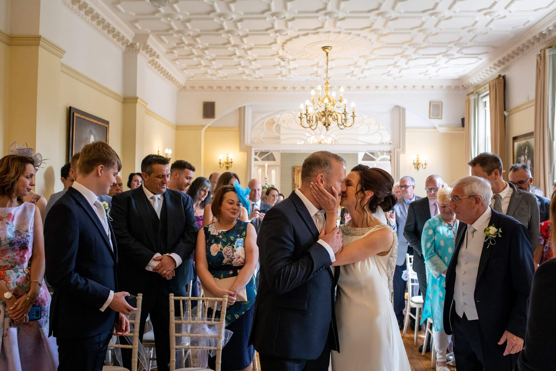 A bride kisses her fiancé at the start of their wedding ceremony