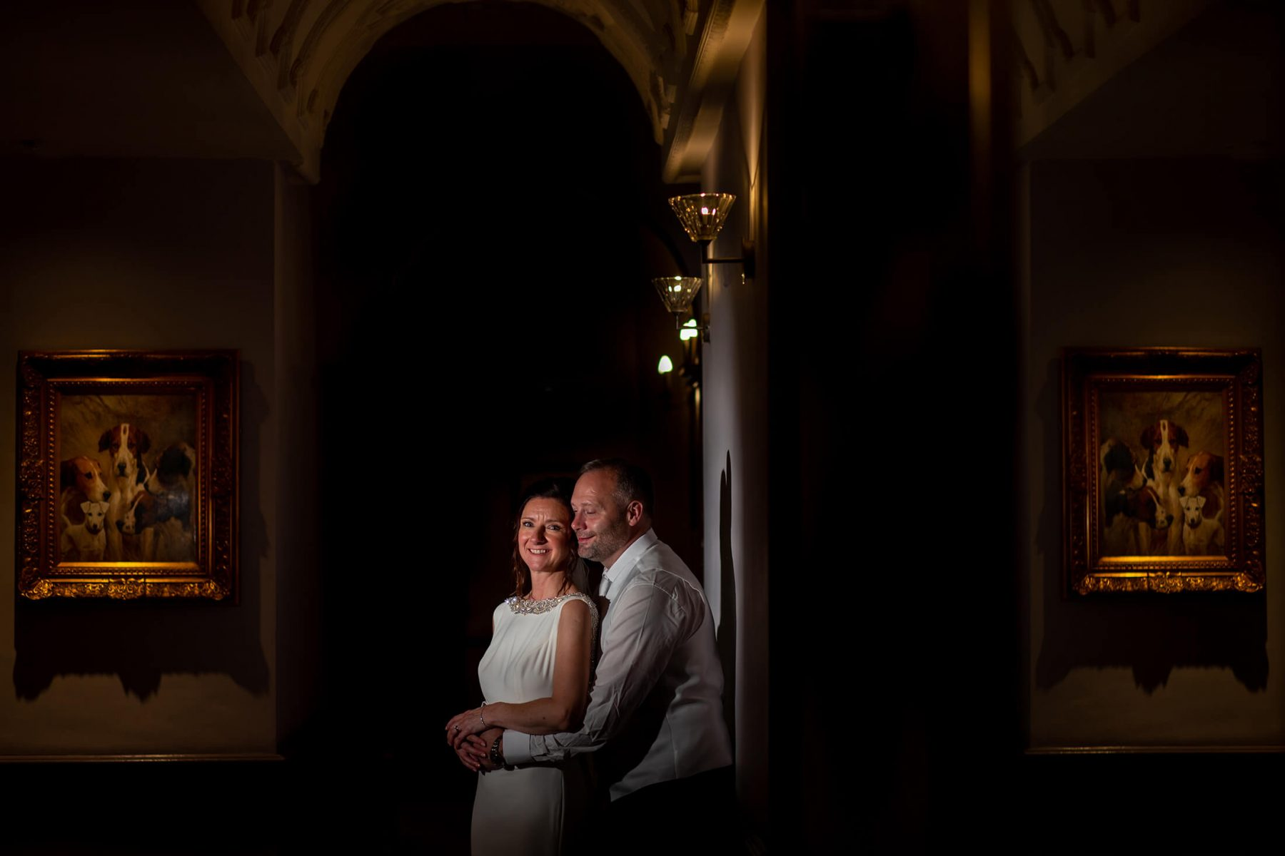 A portrait of the bride and groom in a corridor at Nunsmere Hall.