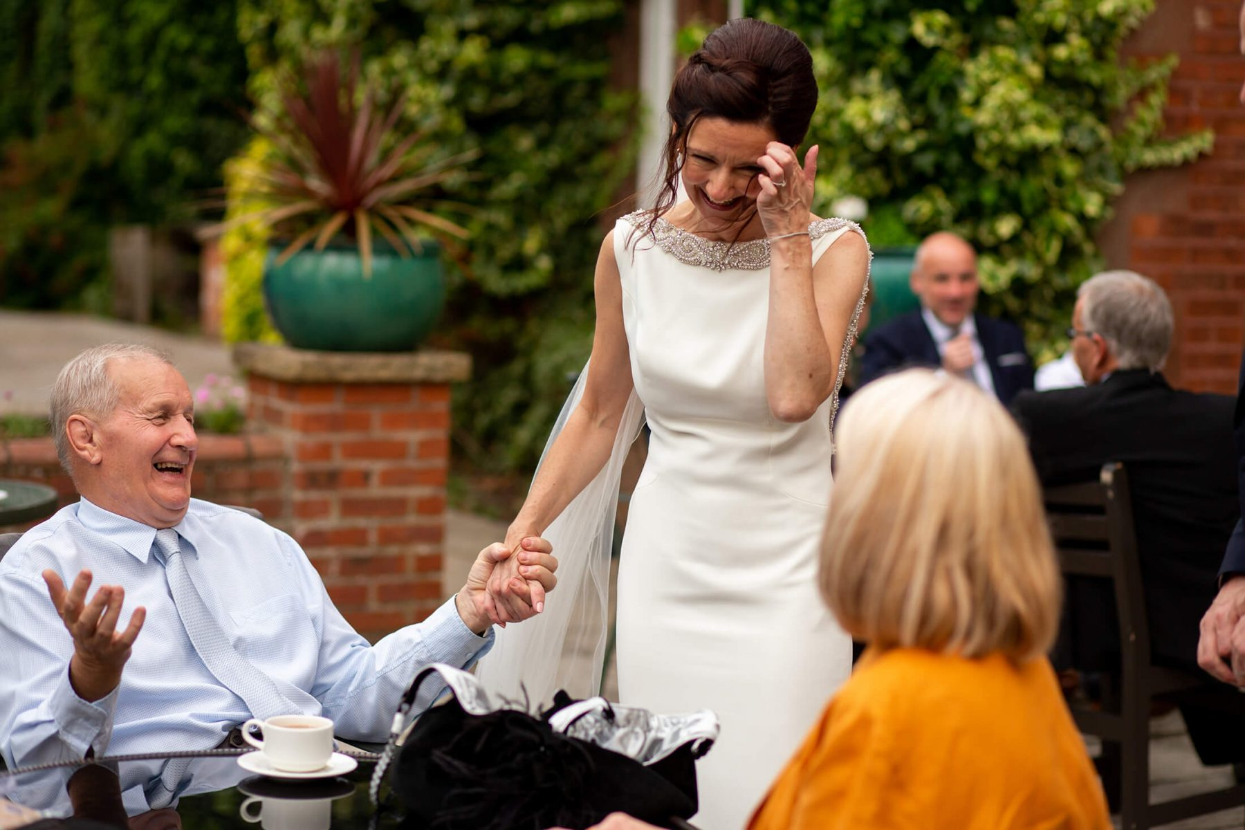 The bride laughs with a wedding guest