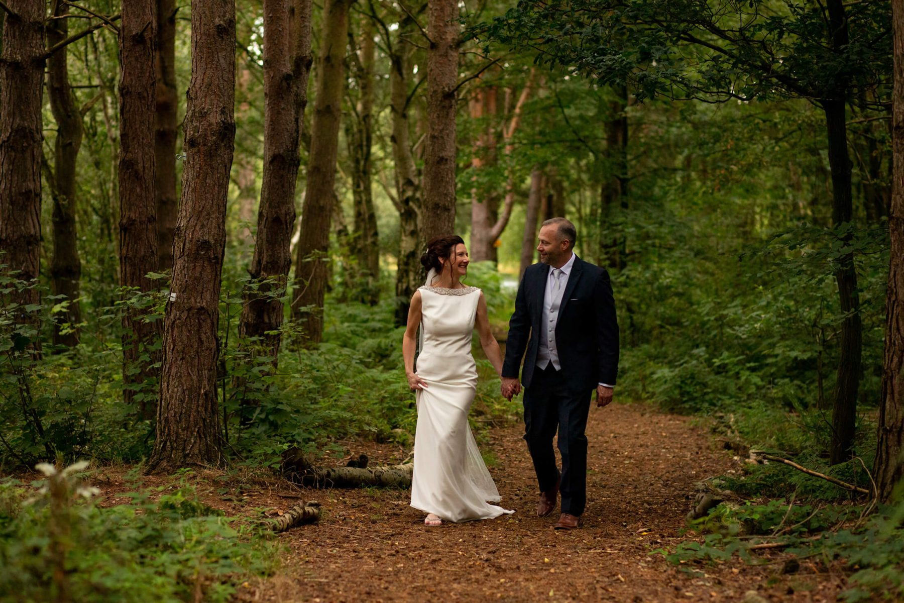 The bride and groom walk through the woods.