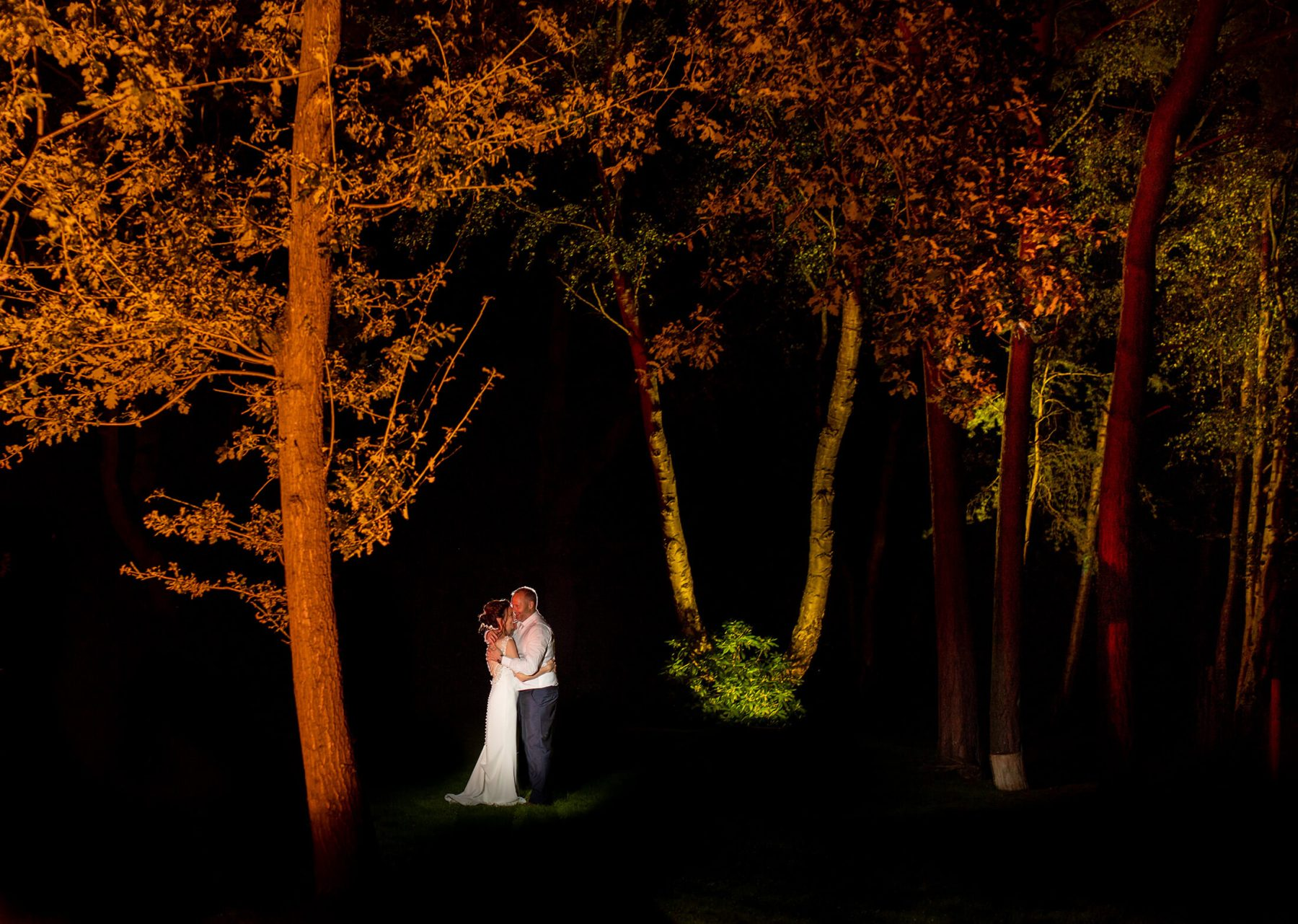 The bride and groom at night surrounded by trees at Nunsmere Hall.