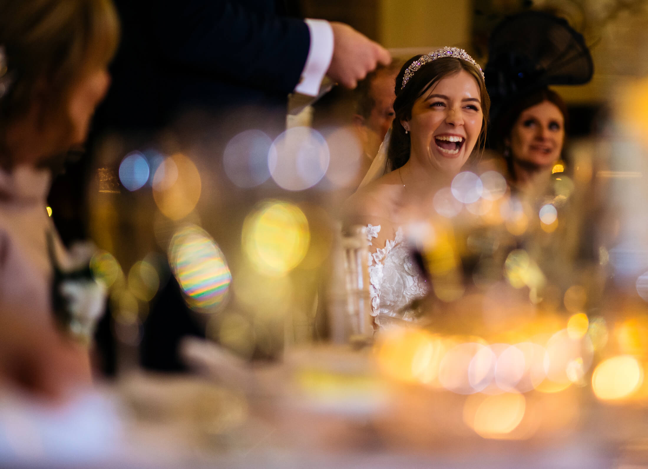 A bride laughs during the speeches at her Peckforton Castle wedding