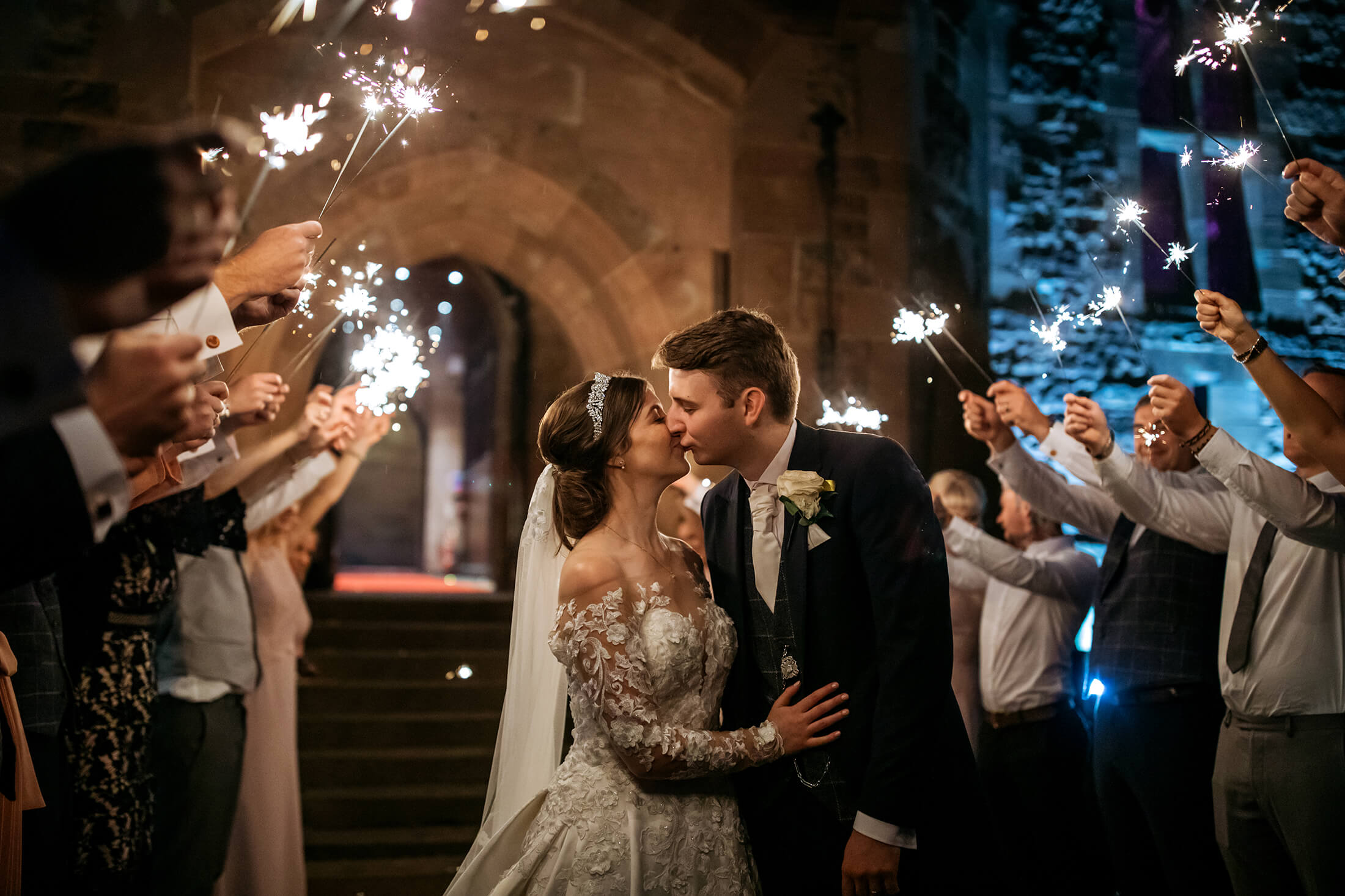 A bride and groom kiss beneath sparklers at Peckforton Castle in Cheshire