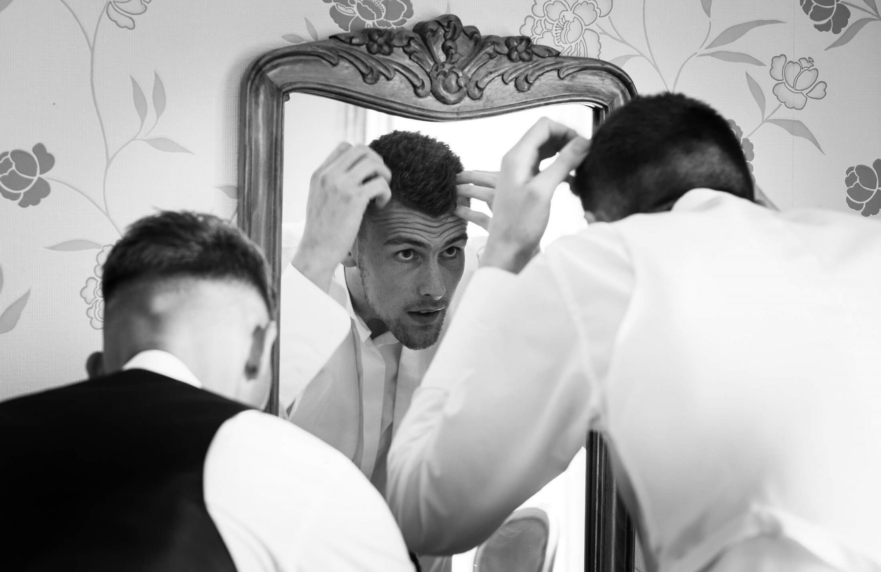 A groom does his hair before the wedding during groom prep