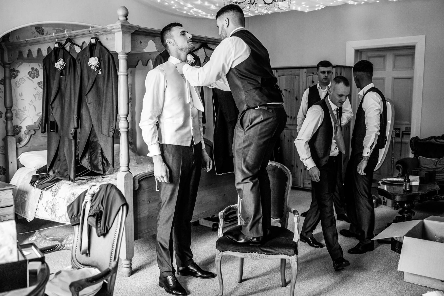 A groom is helped with his suit