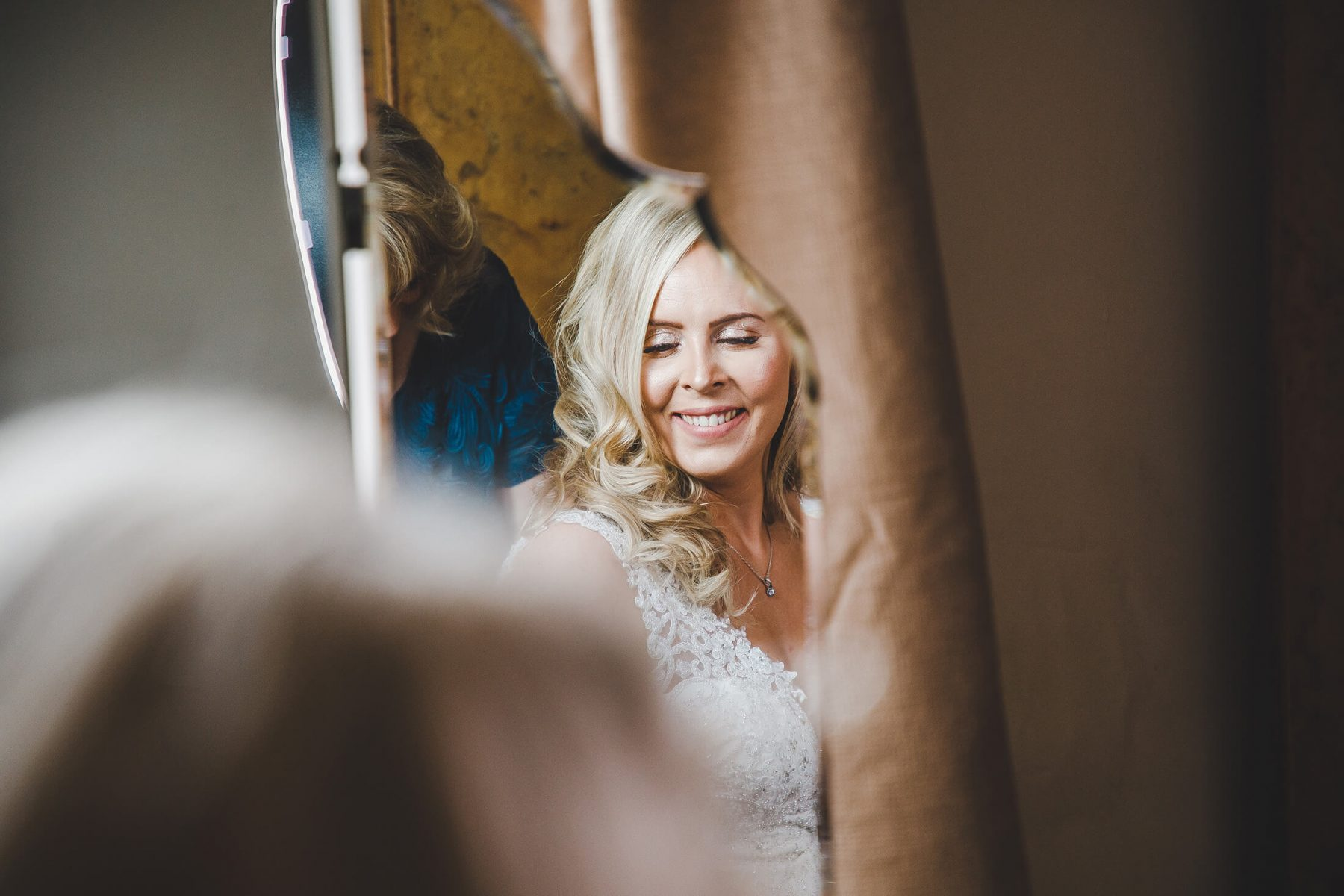 The bride reflected in a mirror during bridal prep