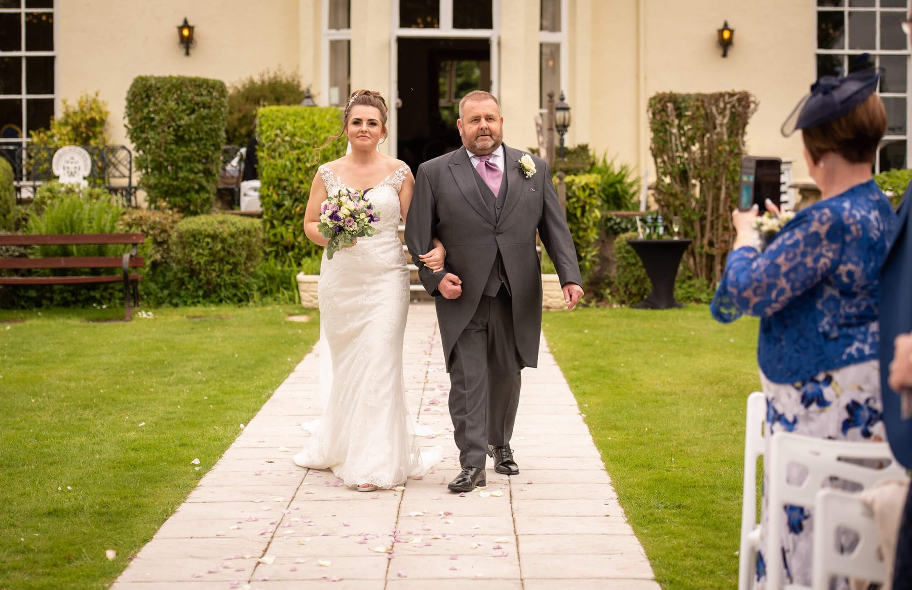 The bride arrives with her father in the gardens for her wedding.