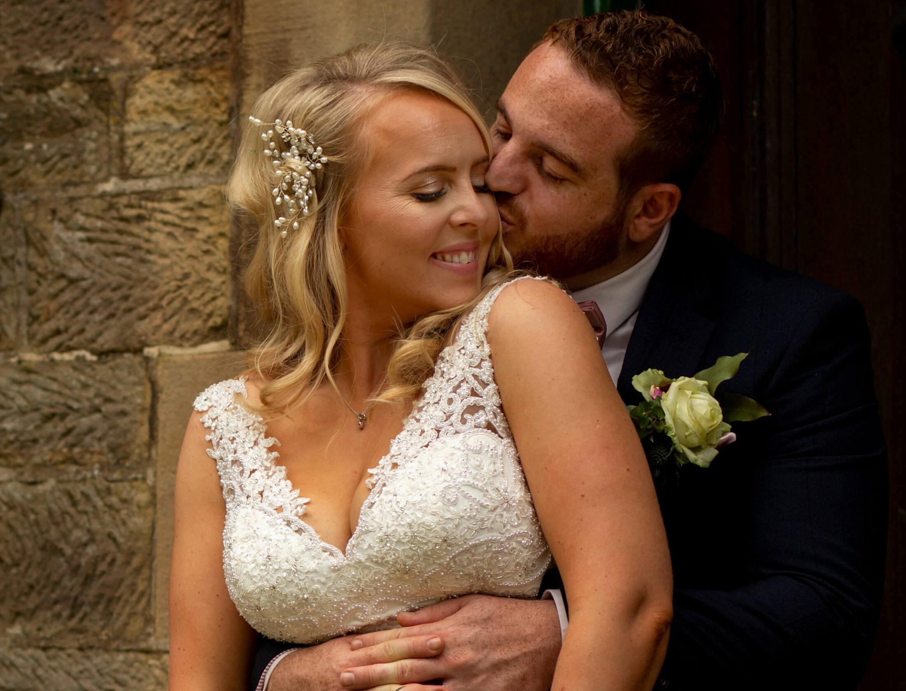 A portrait of a bride and groom sharing a kiss