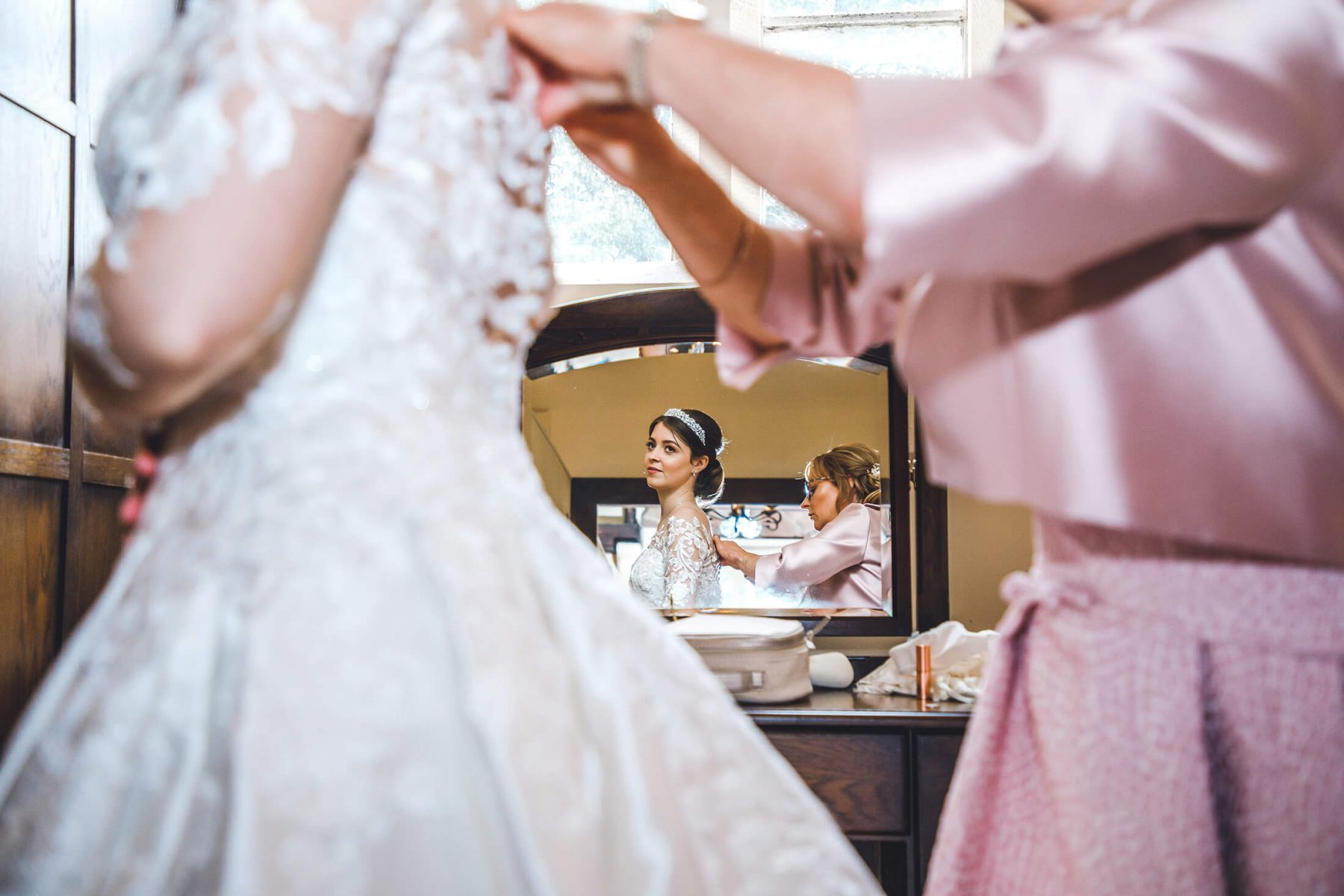 A reflection of a bride in a mirror during bridal prep