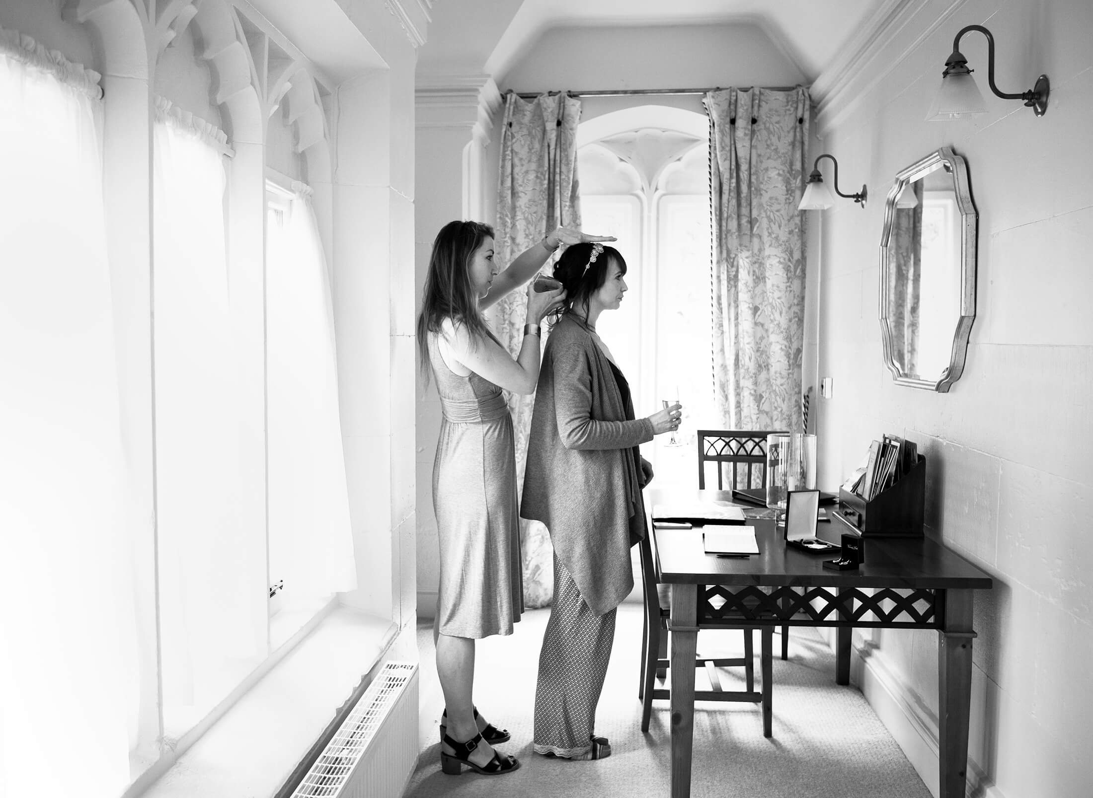 A bride has her hair prepared by a hairdresser before her wedding at Combermere Abbey