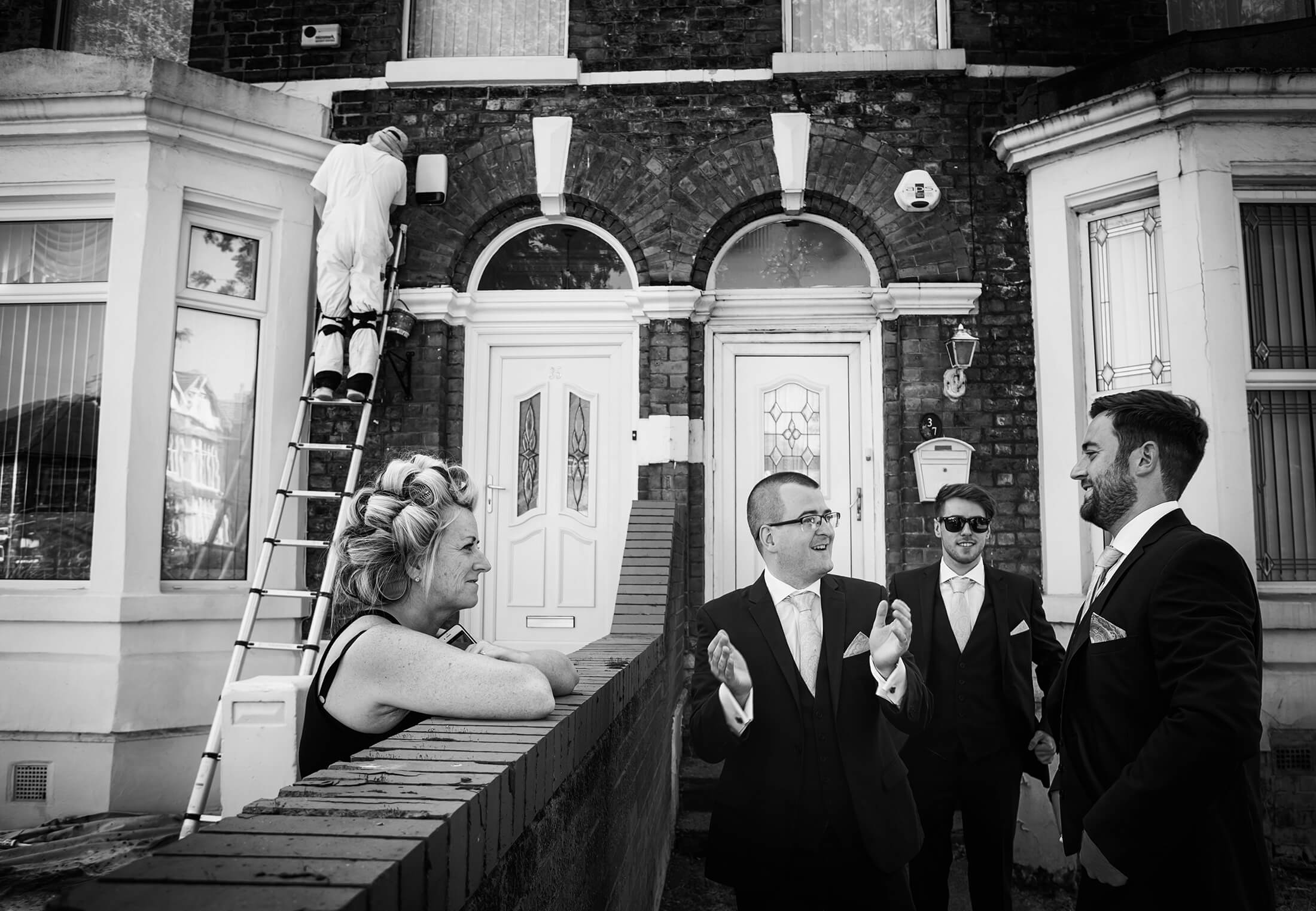 The groom talks to friends and neoighbours before getting married at the Park Hotel in Liverpool - Liverpool Wedding Photography