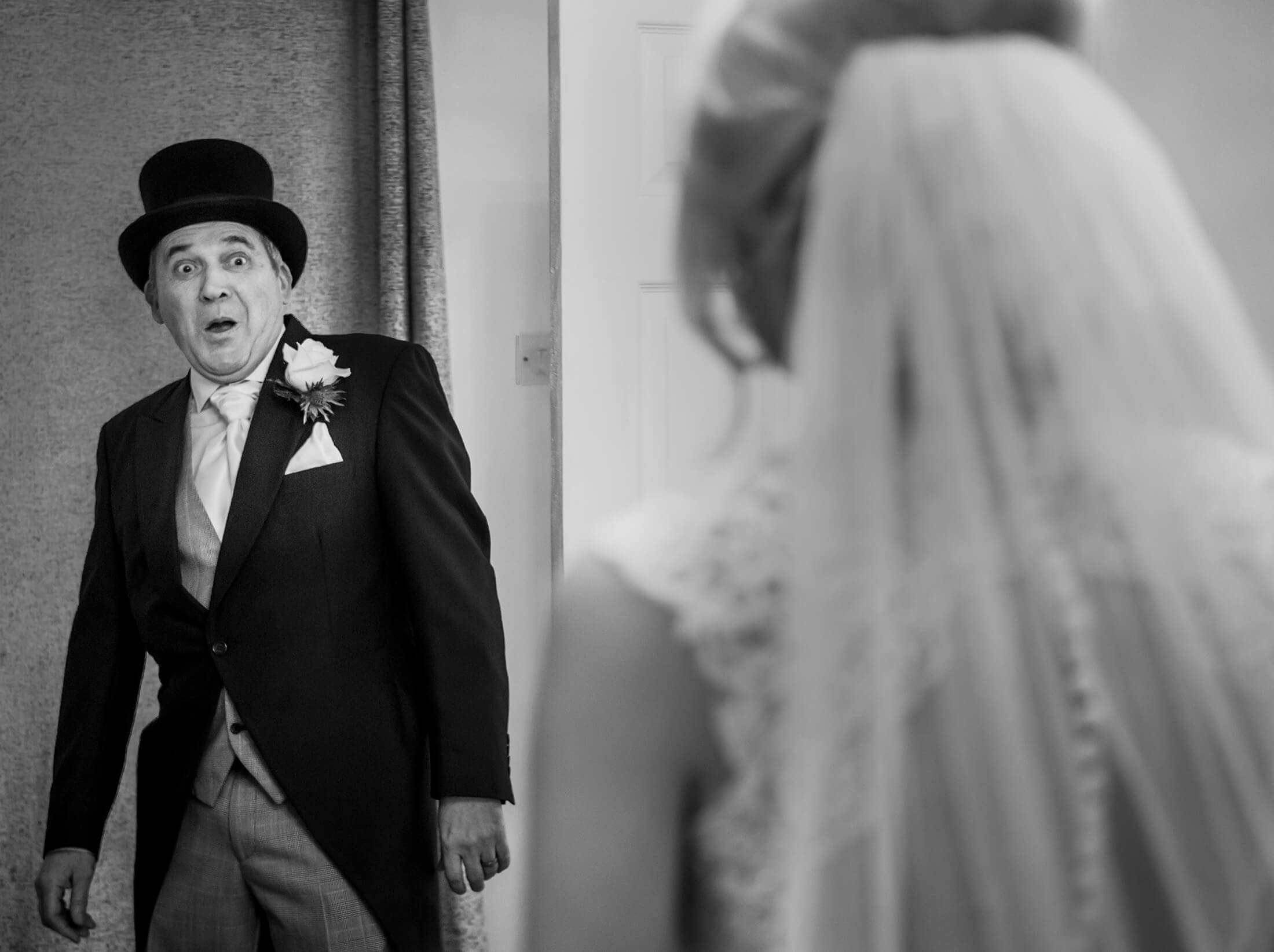 The father of the bride looks surprised as he see his daughter in her wedding dress for the first time. Wychwood Park wedding photographer