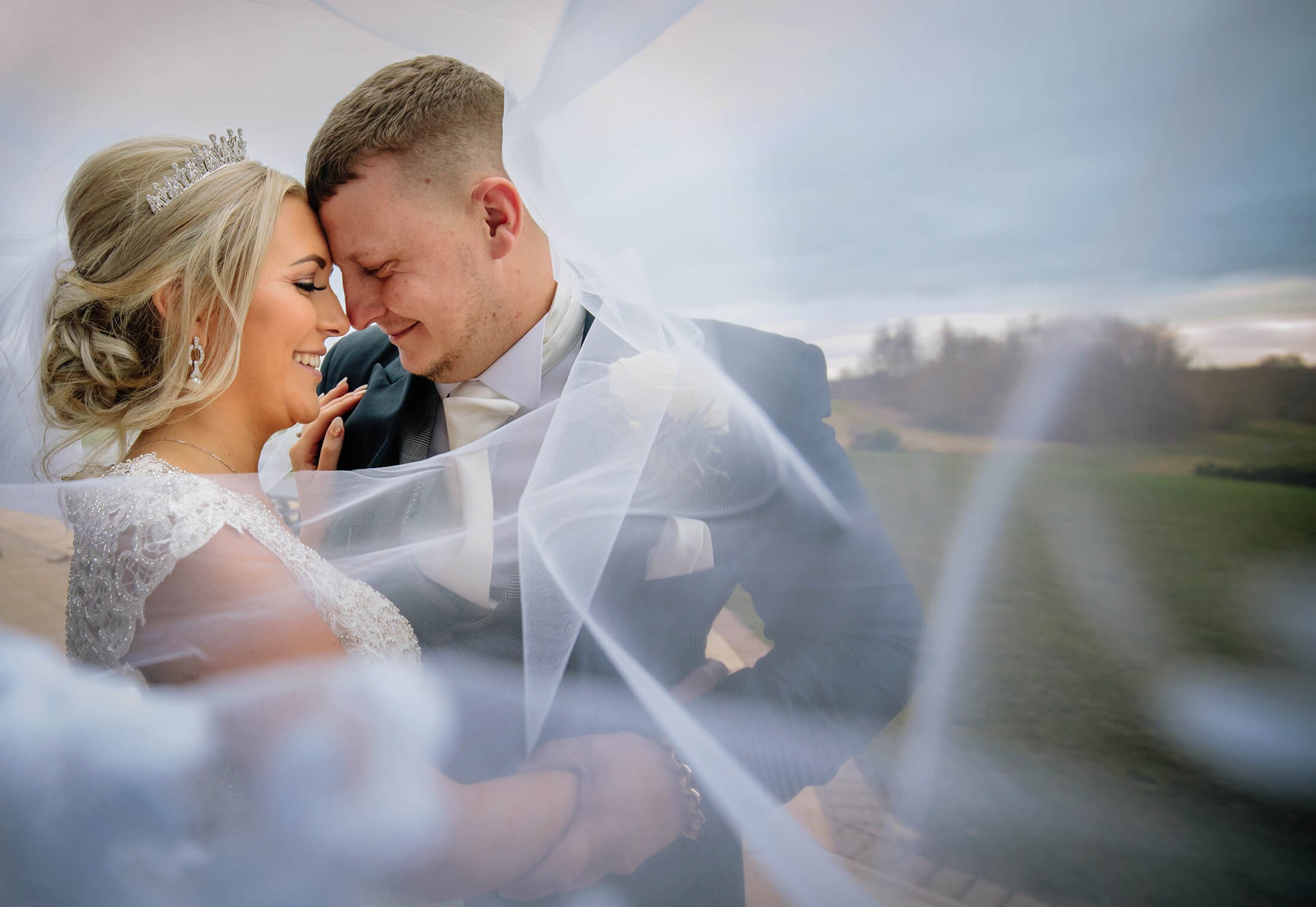 The bride snd groom are wrapped in the brides veil. Wychwood Park wedding photographer