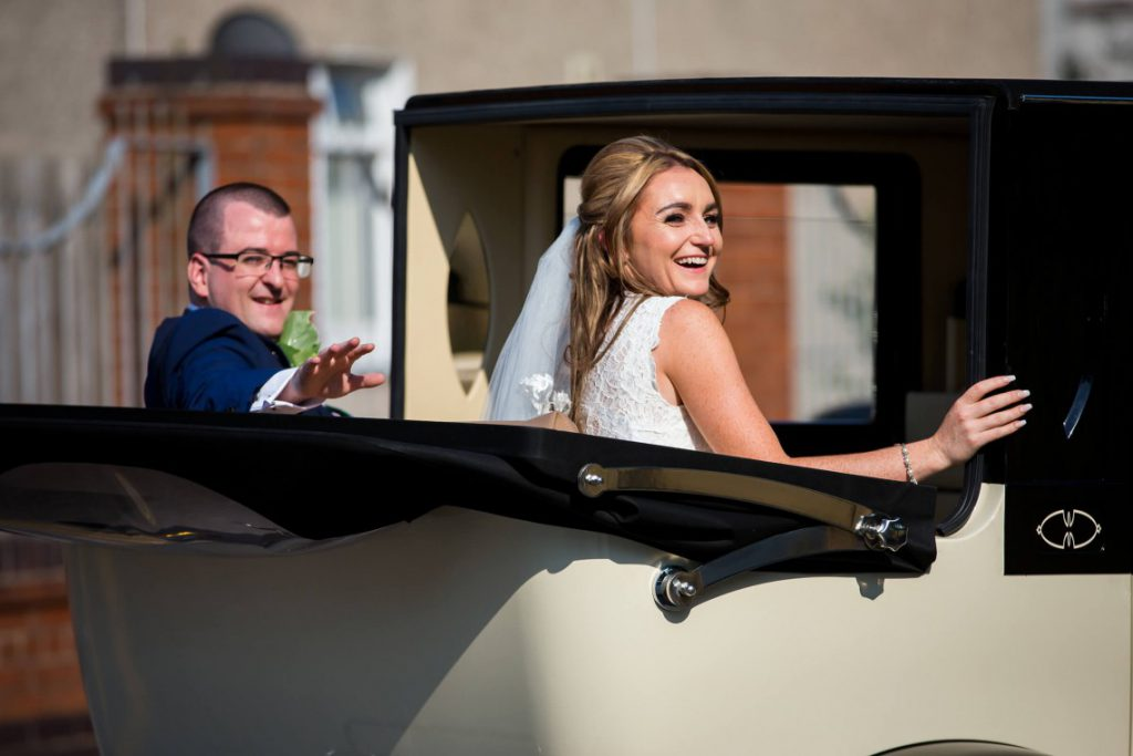 Bride and groom leave in their wedding car