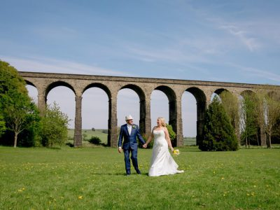 The bride and groom walk in front of a viaduct