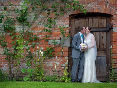 The bride and groom in the gateway at Combermere Abbey