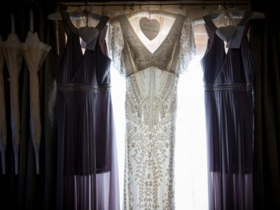The brides' dress hangs in a window