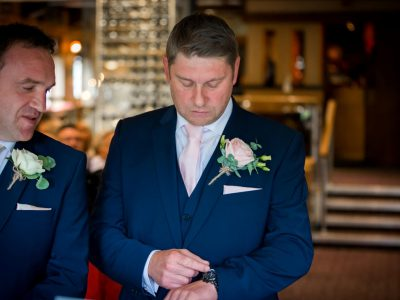 The best man checks his watch as he waits for the bride