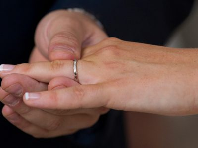 The groom puts a ring on the brides finger